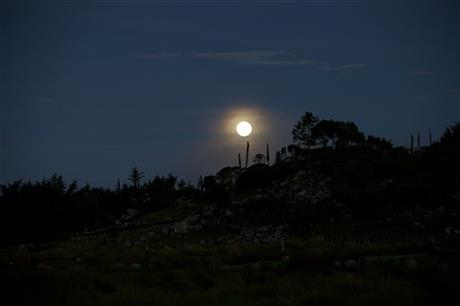 An early morning view of an full moon at Chiantla, in the northern Cuchumatanes mountains of Guatemala, Saturday, July 12, 2014.
