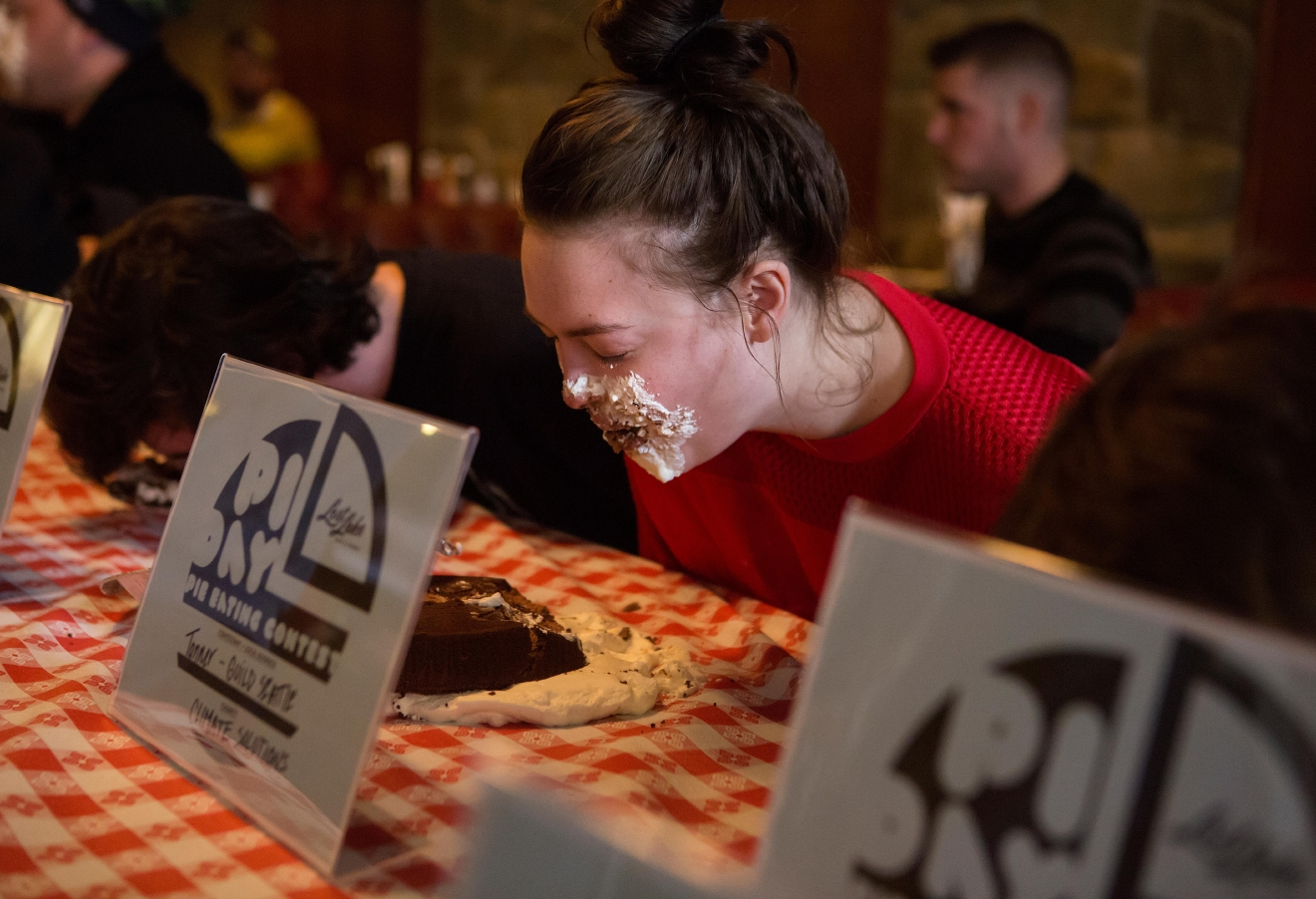 A participant is covered in whip cream as she races to eat her chocolate pie during the second annual Pi Day Pie Eating Contest at Lost Lake Cafe. (Sy Bean / Seattle Refined)