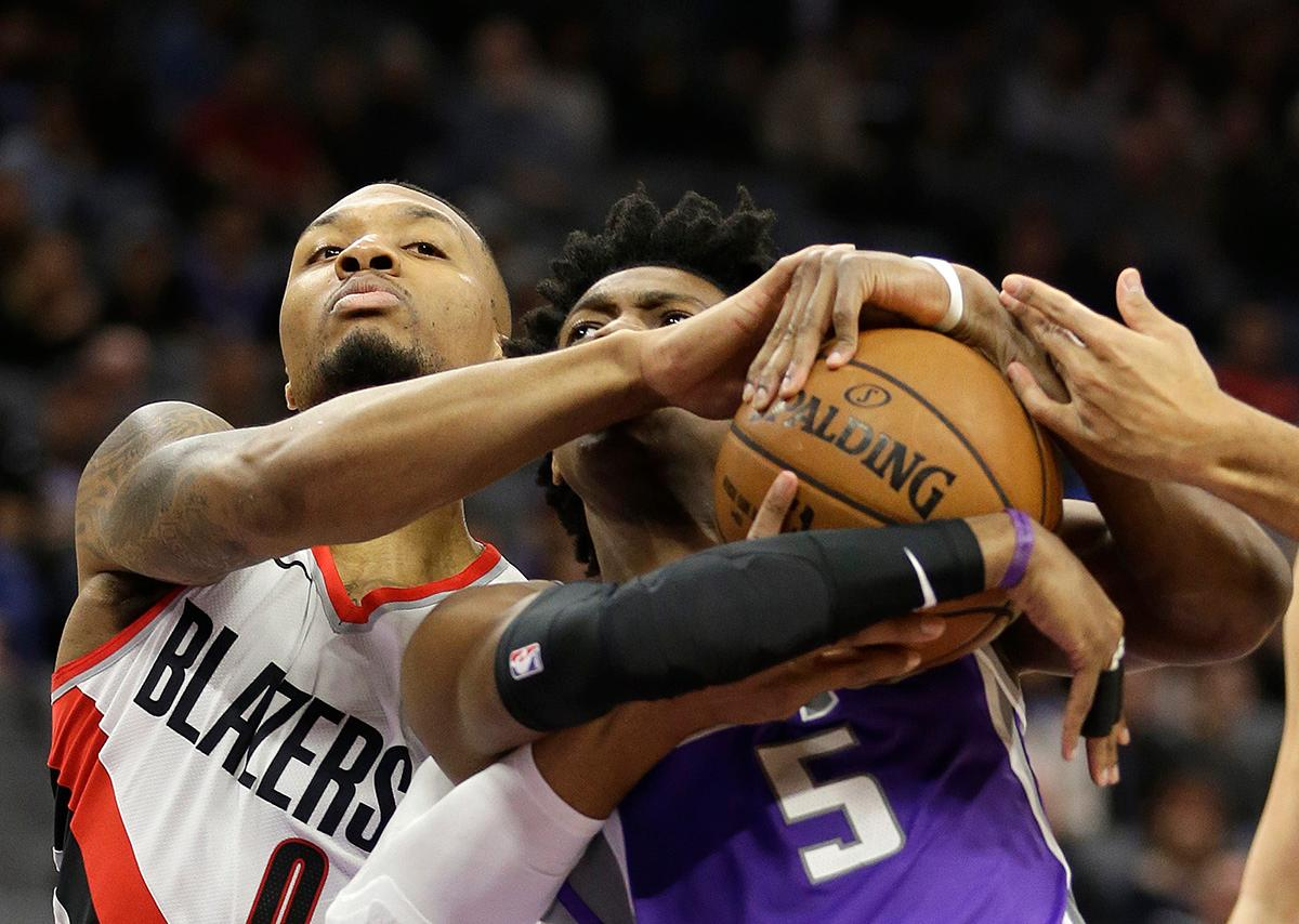 Portland Trail Blazers guard Damian Lillard, left, forces a jump ball with Sacramento Kings guard De'Aaron Fox during the first quarter of an NBA basketball game Friday, Nov. 17, 2017, in Sacramento, Calif. (AP Photo/Rich Pedroncelli)