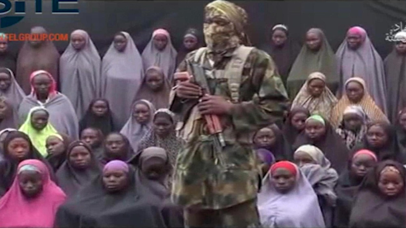 FILE- In this undated image taken from video distributed Sunday, Aug. 14, 2016, an alleged Boko Haram soldier standing in front of a group of girls alleged to be some of the 276 abducted Chibok schoolgirls held since April 2014, in an unknown location.(Militant video/Site Institute via AP File)