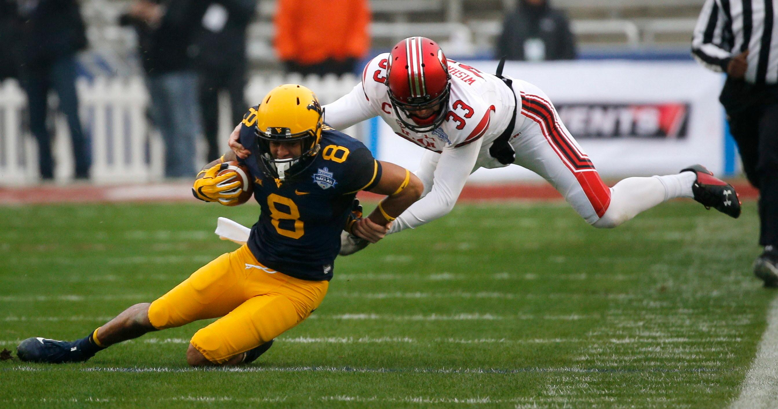 West Virginia wide receiver Marcus Simms (8) is brought down by Utah's Mitch Wishnowsky (33) during the first half of Zaxby's Heart of Dallas Bowl at Cotton Bowl Stadium in Dallas on Tuesday, Dec. 26, 2017. (Rose Baca/The Dallas Morning News via AP)