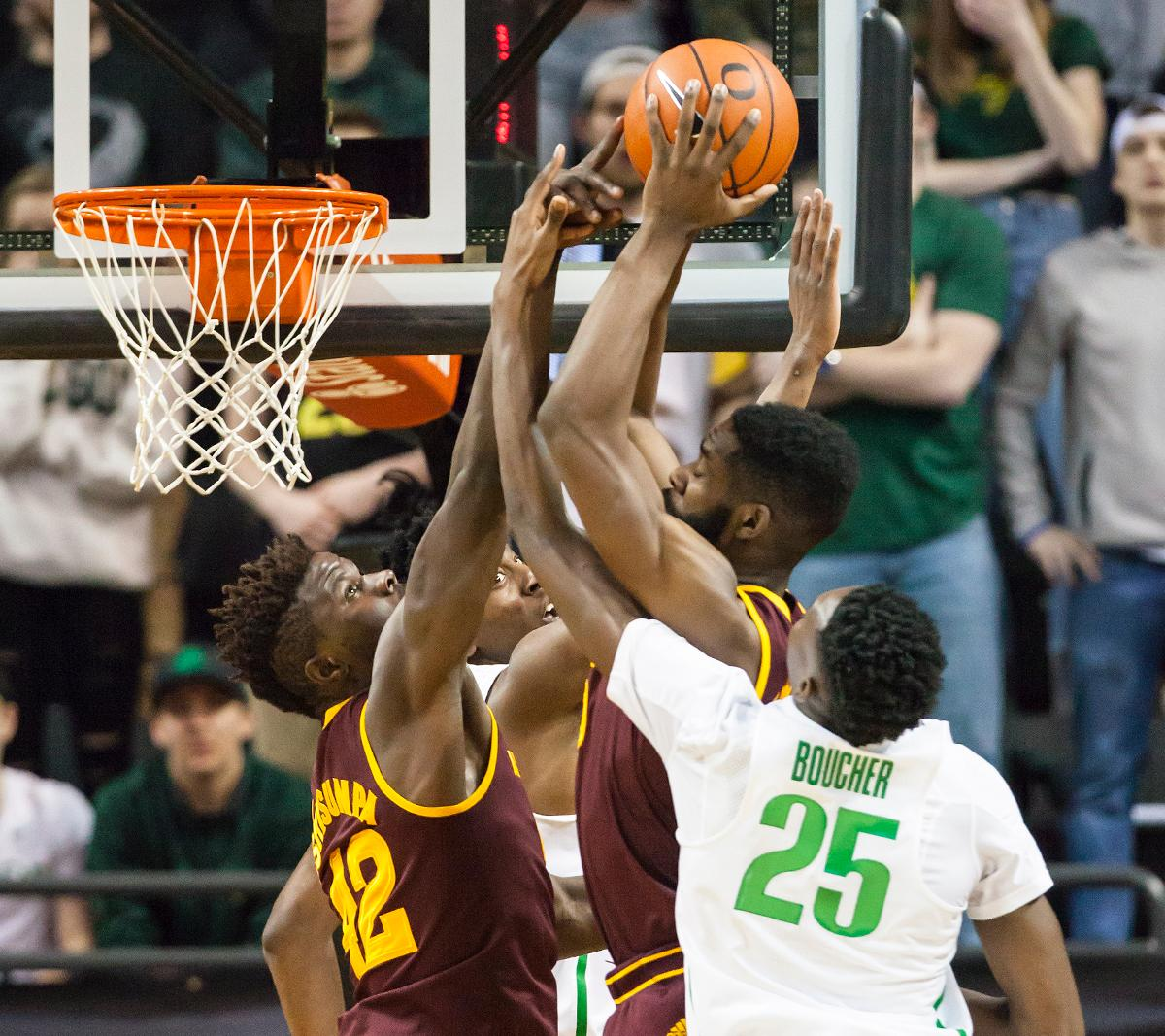 Oregon forward Chis Boucher (#25) leaps to block a shot by Arizona State forward Obinna Oleka (#5). The Oregon Ducks defeated the Arizona State Sun Devils 71 to 70. Photo by Ben Lonergan, Oregon News Lab