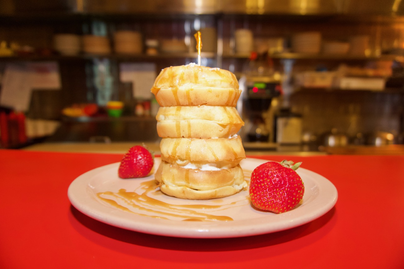 <p>Cheese that's a lot of waffles: Tower of mini waffles with cheesecake filling between each layer and caramel sauce on top / Image: Brian Planalp // Published: 8.15.18</p>