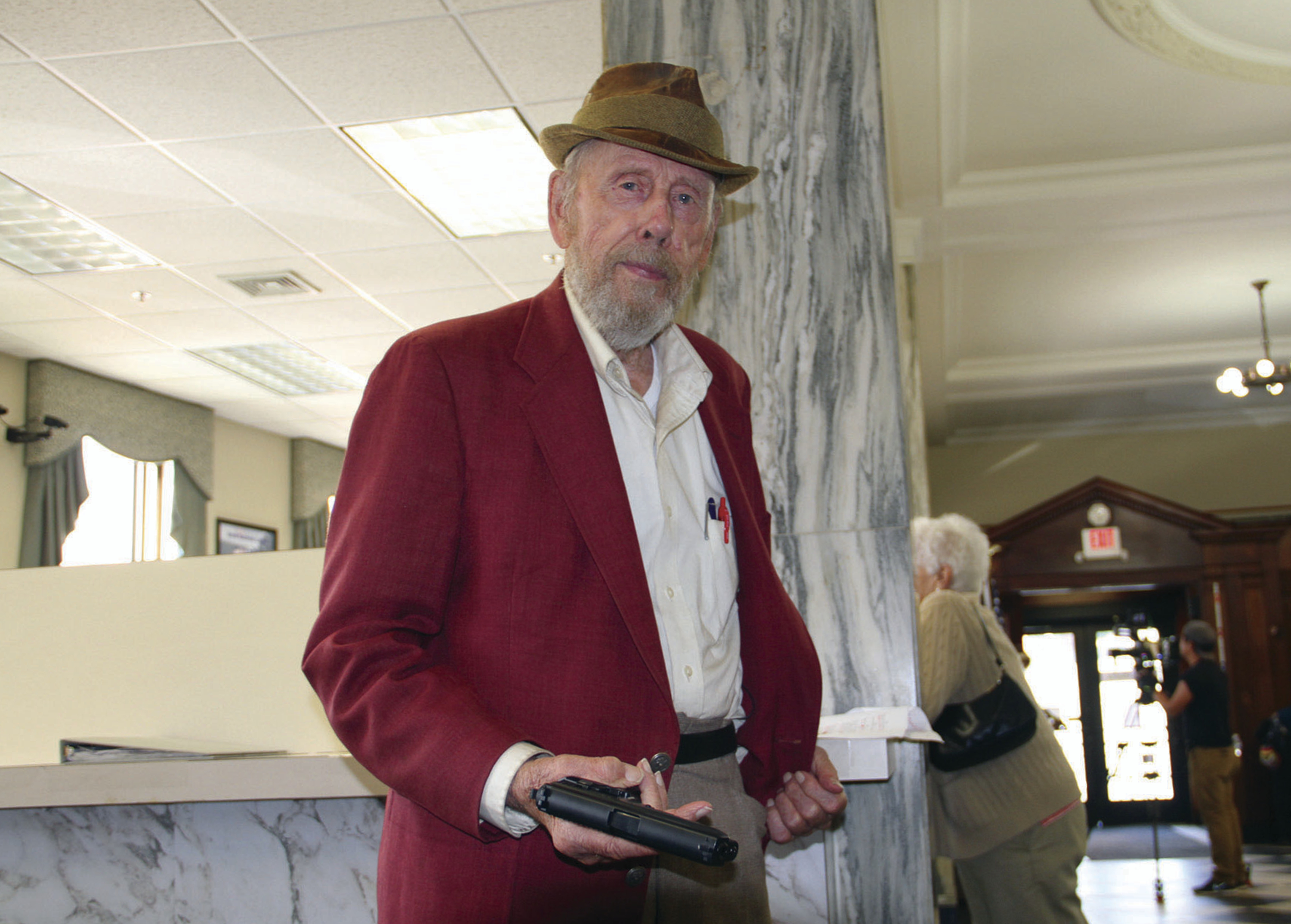 "FILE - In this Sept. 29, 2017, photo, actor Rance Howard flashes a fake pistol prop for the film ""Appleseed,"" in which Howard is costarring, inside Union Bank on Railroad Street in St. Johnsbury, Vt. Director Ron Howard says his actor father Rance Howard has died at age 89. Howard announced his father's passing Saturday, Nov. 25, 2017, on Twitter. He praised his father for his ability to balance ambition with great personal integrity.  (Dana Gray/Caledonian-Record via AP, File)"