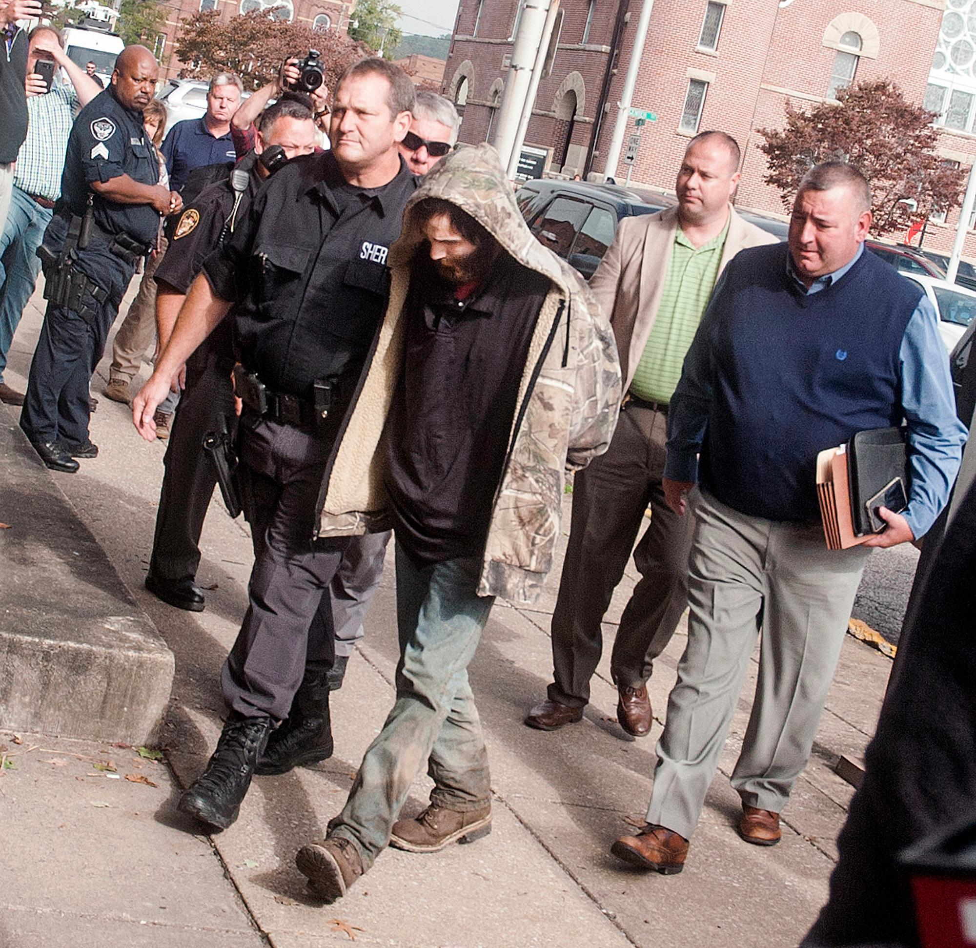 Suspect Arron Lawson, center, is escorted into the Lawrence County Courthouse, Friday Oct. 13, 2017 by Sheriff Jeff Lawless, left, and detectives Jason Newman and Aaron Bollinger, pictured on far right, of the Lawrence County Sheriff's Office in Ironton, Ohio. Lawson is being held on charges of murder and aggravated murder. (Jessica St. James/Ironton Tribune via AP)