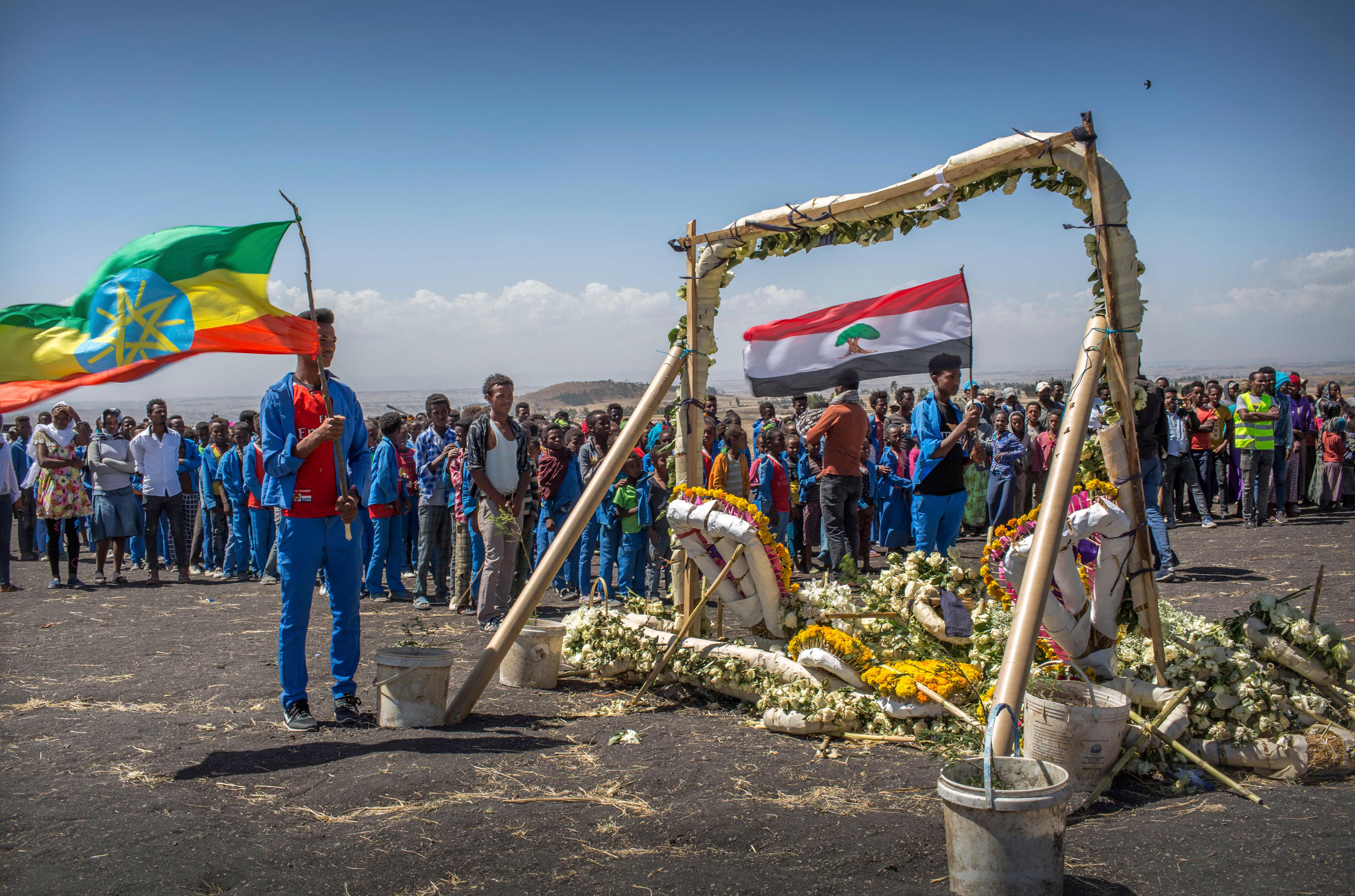 Students from Hama elementary school, who walked an hour and a half from their school in the surrounding area to pay their respects, stand next to floral tributes at the scene where the Ethiopian Airlines Boeing 737 Max 8 crashed shortly after takeoff on Sunday killing all 157 on board, near Bishoftu, south-east of Addis Ababa, in Ethiopia Friday, March 15, 2019. (AP Photo/Mulugeta Ayene)