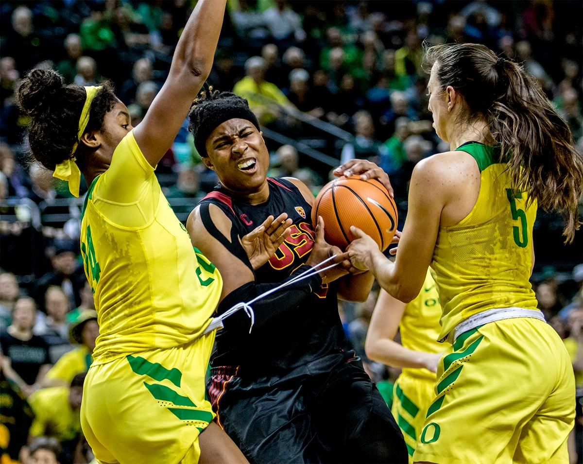 The Trojan's Kristen Simon (#35) grimaces as she tries to push past the Ducks to the basket. The Oregon Ducks defeated the USC Trojans 80-74 on Friday at Matthew Knight Arena in a  game that went into double overtime. Lexi Bando sealed the Ducks victory by scoring a three-pointer in the closing of the game. Ruthy Hebard set a new NCAA record of 30 consecutive field goals, the old record being 28. Ruthy Hebard got a double-double with 27 points and 10 rebounds, Mallory McGwire also had 10 rebounds. The ducks had four players in double digits. The Ducks are now 24-4, 13-2 in the Pac-12, and are tied for first with Stanford. Photo by August Frank, Oregon News Lab