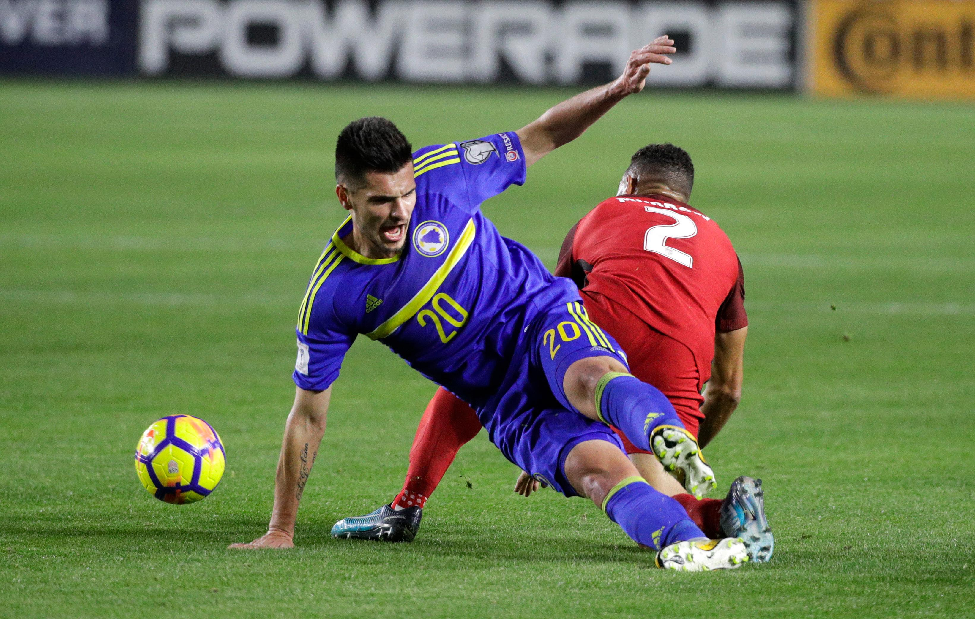Bosnia and Herzegovina midfielder Goran Zakaric, left, and United States defender Justin Morrow tumble as they fight for the ball during the first half of an international friendly soccer match on Sunday, Jan. 28, 2018, in Carson, Calif. (AP Photo/Jae C. Hong)