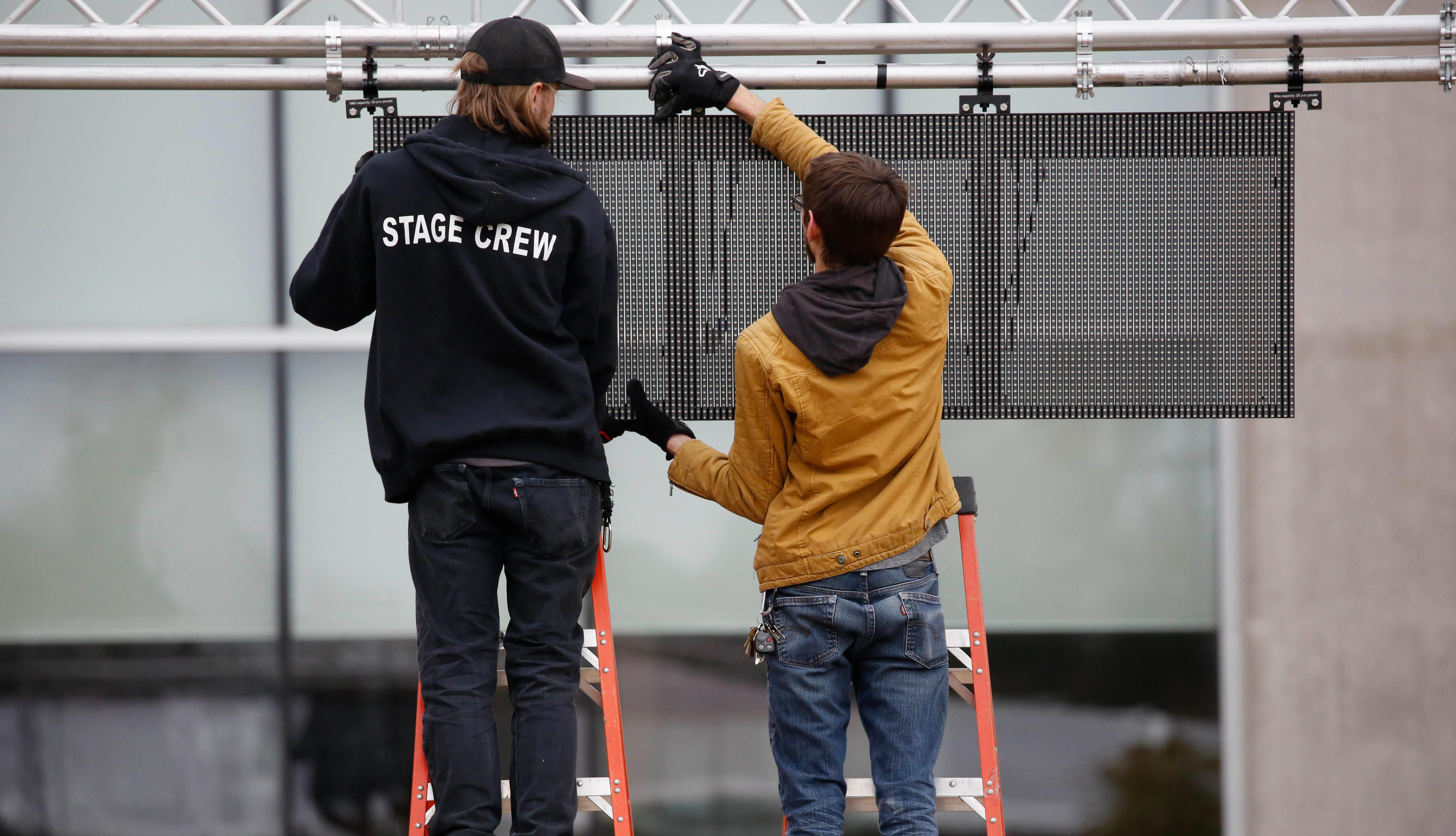Workmen construct a lighted panel near the stage before the state's two newest museums, the Museum of Mississippi History and the Mississippi Civil Rights Museum, Thursday, Dec. 7, 2017 in Jackson, Miss. The stage will play host to a day of musical acts as well as the opening ceremony for the museums. The long-planned Saturday ceremony will mark Mississippi's bicentennial of admission into the union, however the appearance of President Donald Trump at the ceremony has drawn the ire of U.S. Reps. John Lewis, D-Ga., and Bennie Thompson, D-Miss., who announced Thursday they won't attend the opening of Mississippi civil rights and history museums. What was intended as a moment of racial unity and atonement in the state with the largest share of African-Americans is descending into racial and partisan strife after Republican Mississippi Gov. Phil Bryant invited fellow Republican Trump to attend. (AP Photo/Rogelio V. Solis)