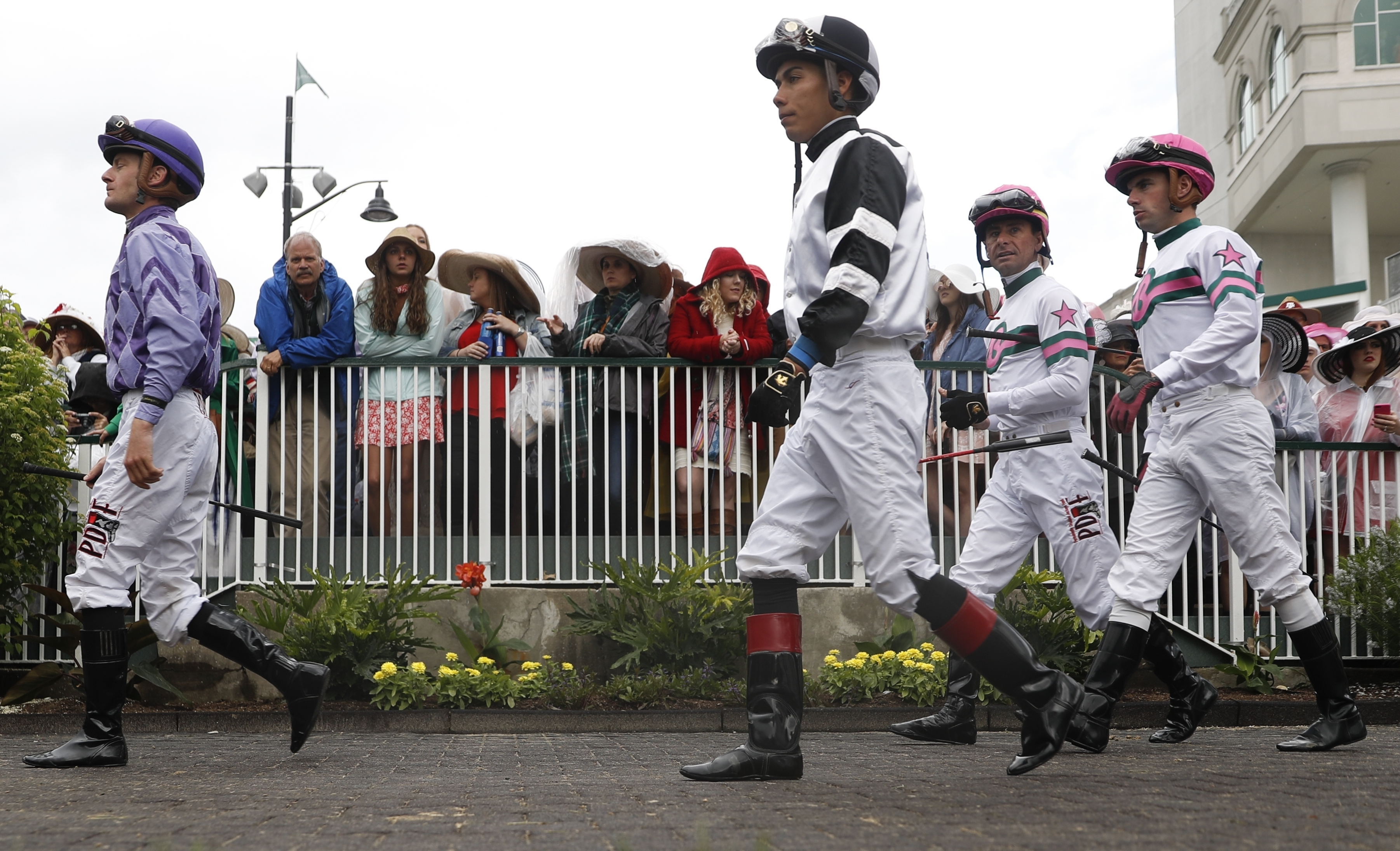Some jockeys walk through the paddock in a race before the 143rd running of the Kentucky Derby horse race at Churchill Downs Saturday, May 6, 2017, in Louisville, Ky. (AP Photo/John Minchillo)