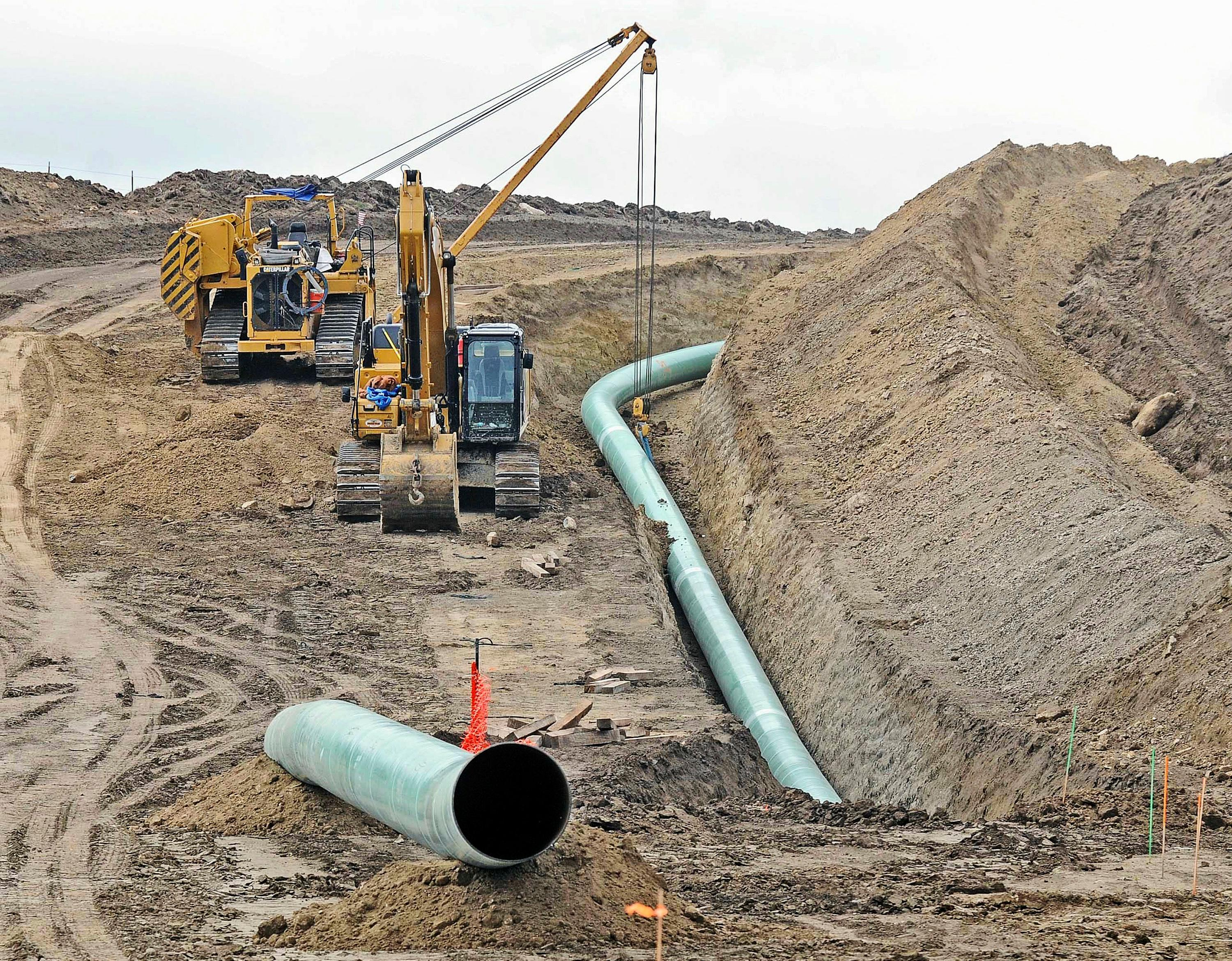 FILE - In this Oct. 5, 2016, file photo, heavy equipment is seen at a site where sections of the Dakota Access pipeline were being buried near the town of St. Anthony in Morton County, N.D. The 1,200-mile line carrying North Dakota oil through South Dakota and Iowa to a distribution point in Illinois began commercial service Thursday, June 1, 2017. (Tom Stromme/The Bismarck Tribune via AP, File)