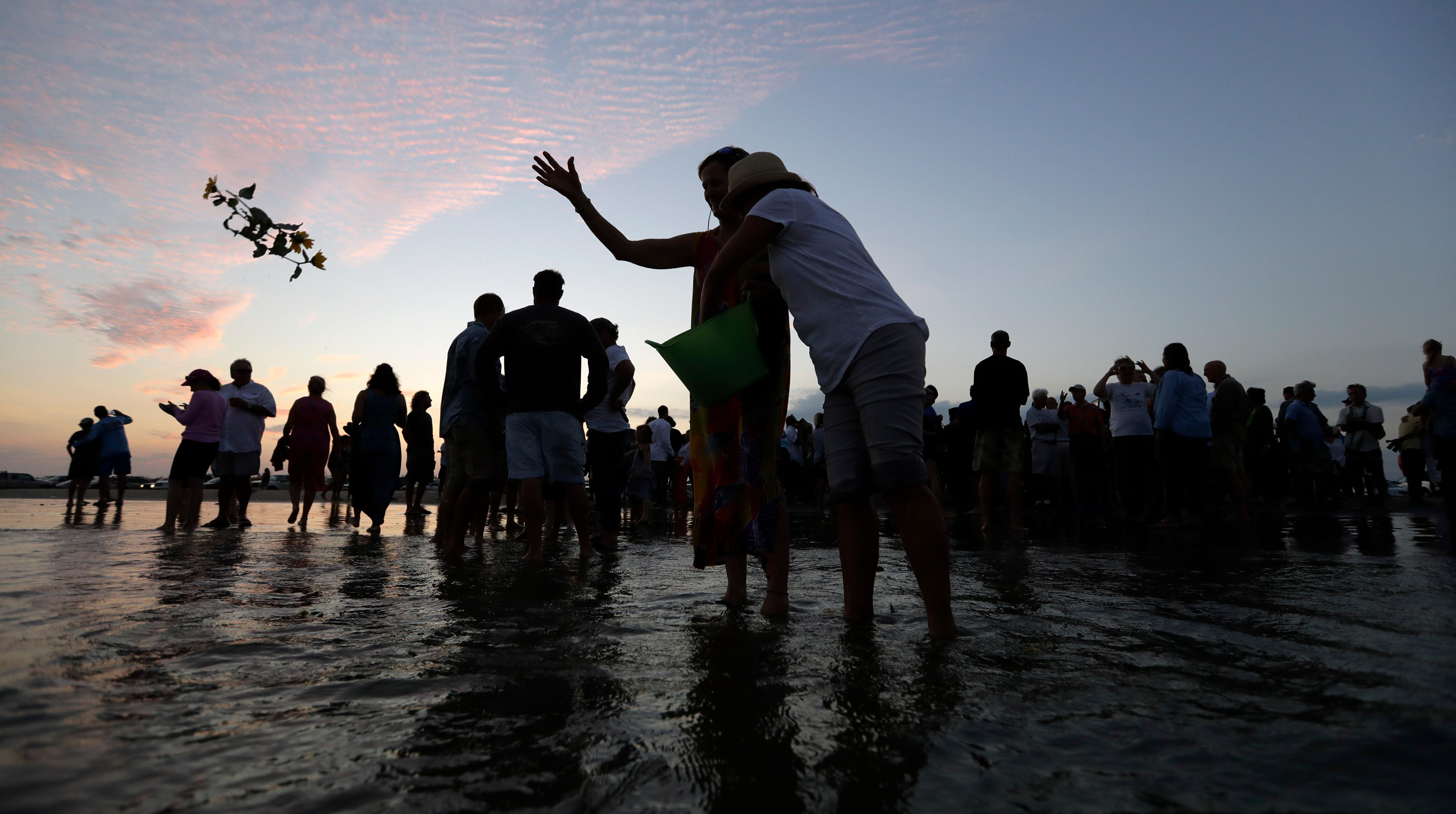 Flowers are tossed in to ocean after a sea turtle with along with the ashes of renowned oceanographer Tony Amos were released into the Gulf of Mexico following a memorial service, Saturday, Sept. 30, 2017, in Port Aransas, Texas. Amos, 80, died of complications from prostate cancer on Sept. 4, mere days after Harvey roared ashore as a fearsome hurricane.  (AP Photo/Eric Gay)