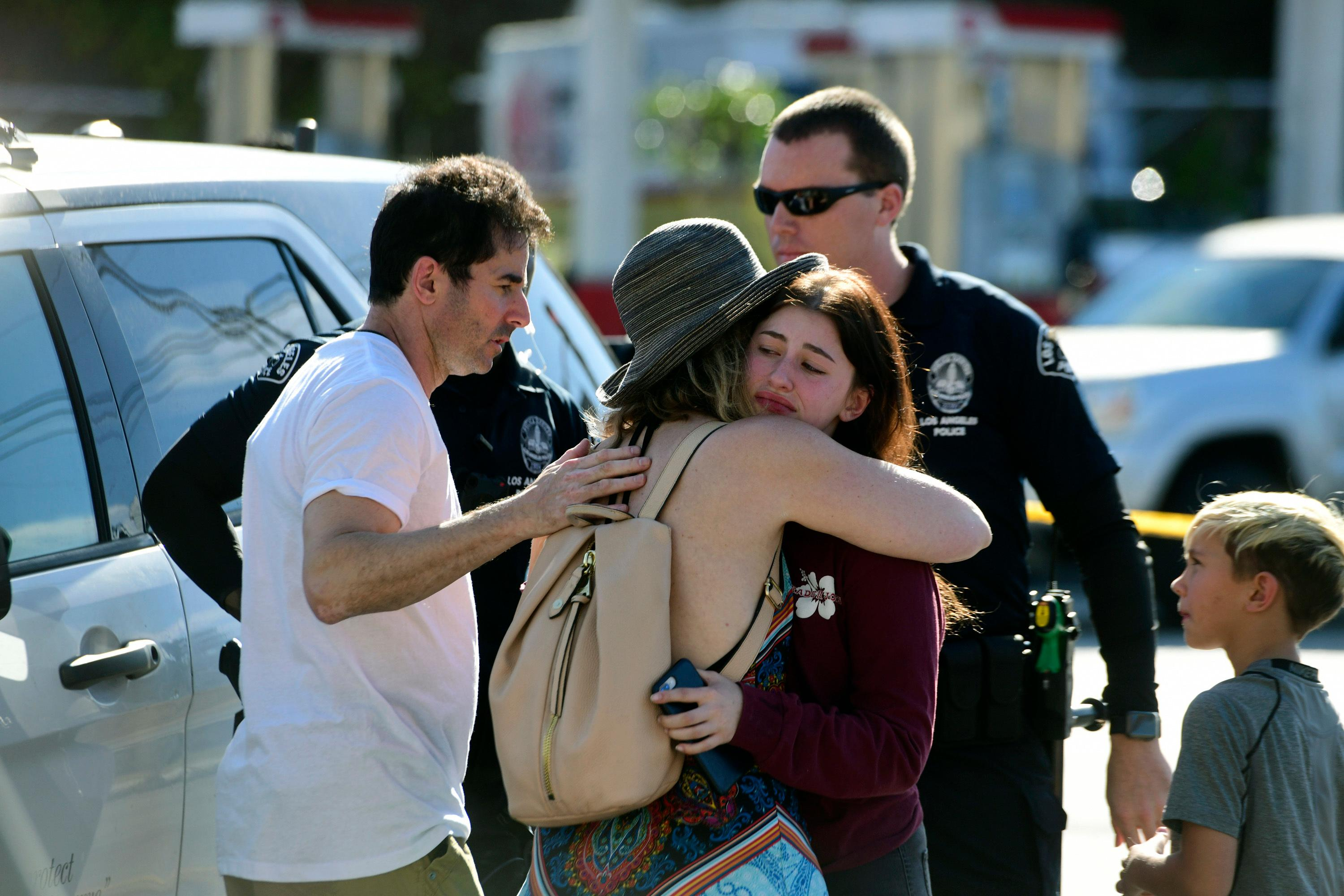 In this photo provided by Christian Monterrosa, a Trader Joe's employee, right, hugs her loved after a gunman held dozens of people hostage  inside a Trader Joe's supermarket before handcuffing himself and surrendering to police, Saturday, July 21, 2018, in Los Angeles.  (Christian Monterrosa via AP)