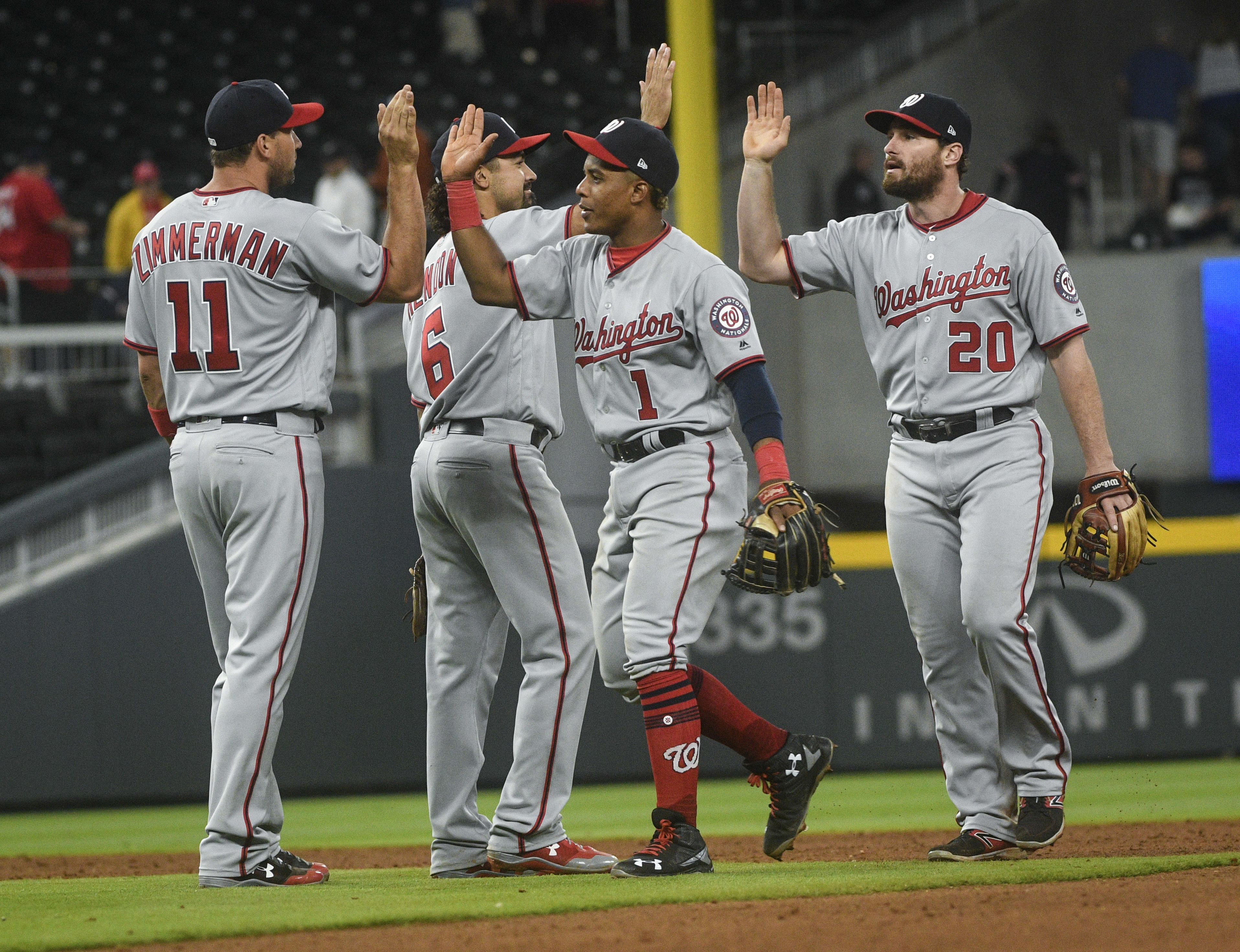 Washington Nationals' Ryan Zimmerman (11), Anthony Rendon (6), Wilmer Difo (1) and Daniel Murphy (20) celebrate after a baseball game against the Atlanta Braves, Tuesday, April 18, 2017, in Atlanta. Washington won 3-1. (AP Photo/John Amis)
