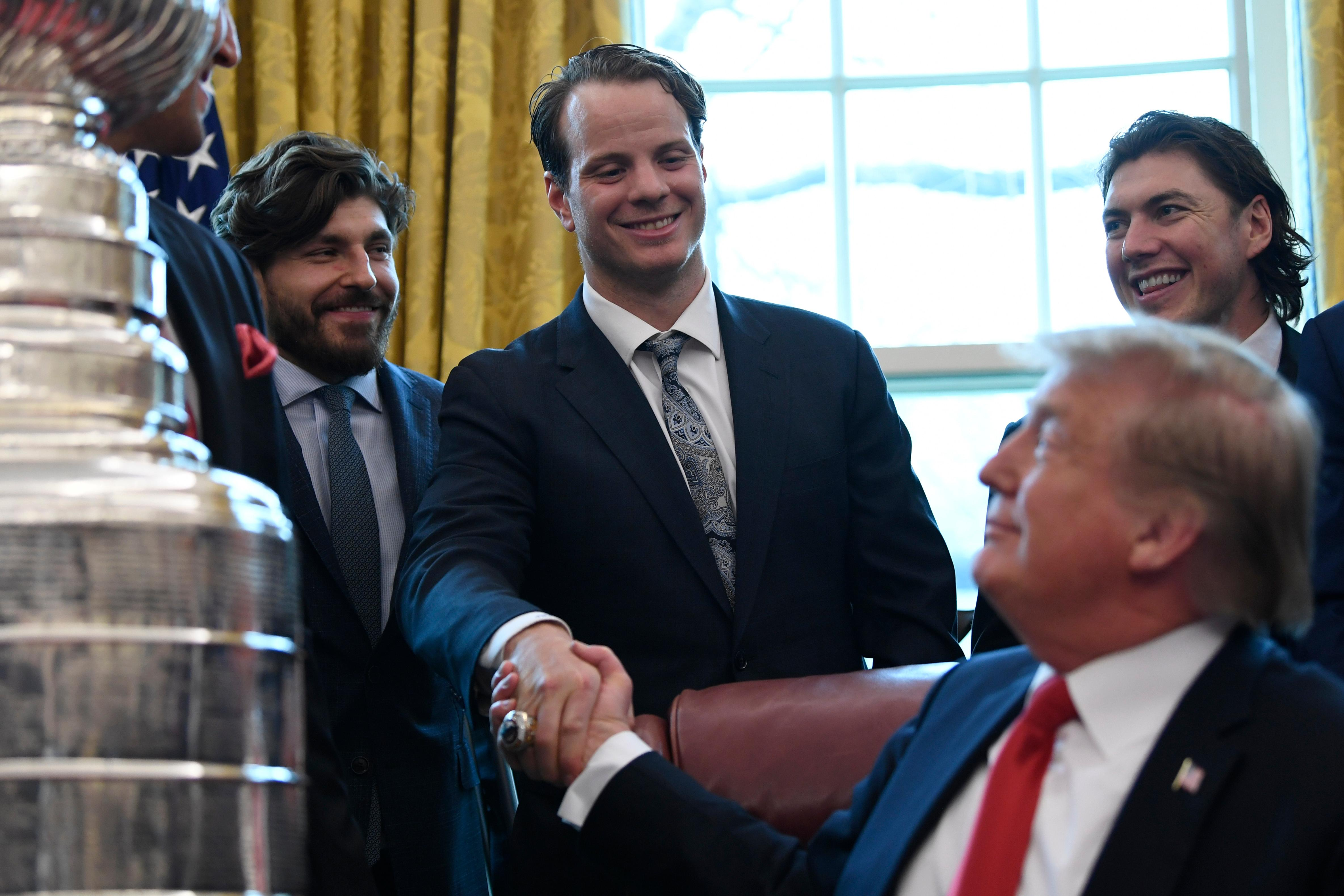 President Donald Trump, front right, shakes hands with John Carlson of the 2018 Stanley Cup Champion Washington Capitals hockey team in the Oval Office of the White House in Washington, Monday, March 25, 2019. Teammate T.J. Oshie watches at right. (AP Photo/Susan Walsh)