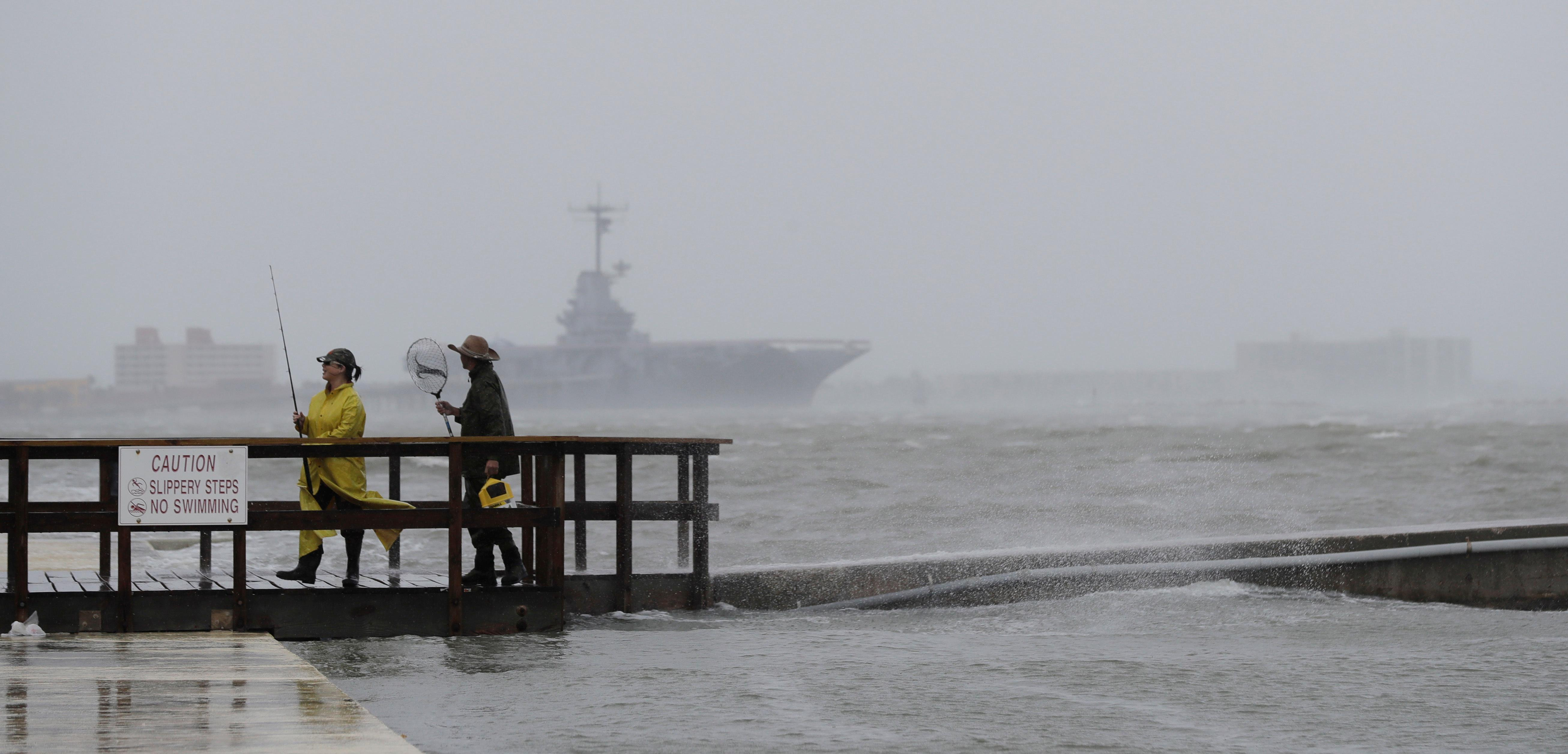 Fishermen walk along a pier as the early bands of Hurricane Harvey make landfall, Friday, Aug. 25, 2017, in Corpus Christi, Texas. Harvey intensified into a hurricane Thursday and steered for the Texas coast with the potential for up to 3 feet of rain, 125 mph winds and 12-foot storm surges in what could be the fiercest hurricane to hit the United States in almost a dozen years.(AP Photo/Eric Gay)