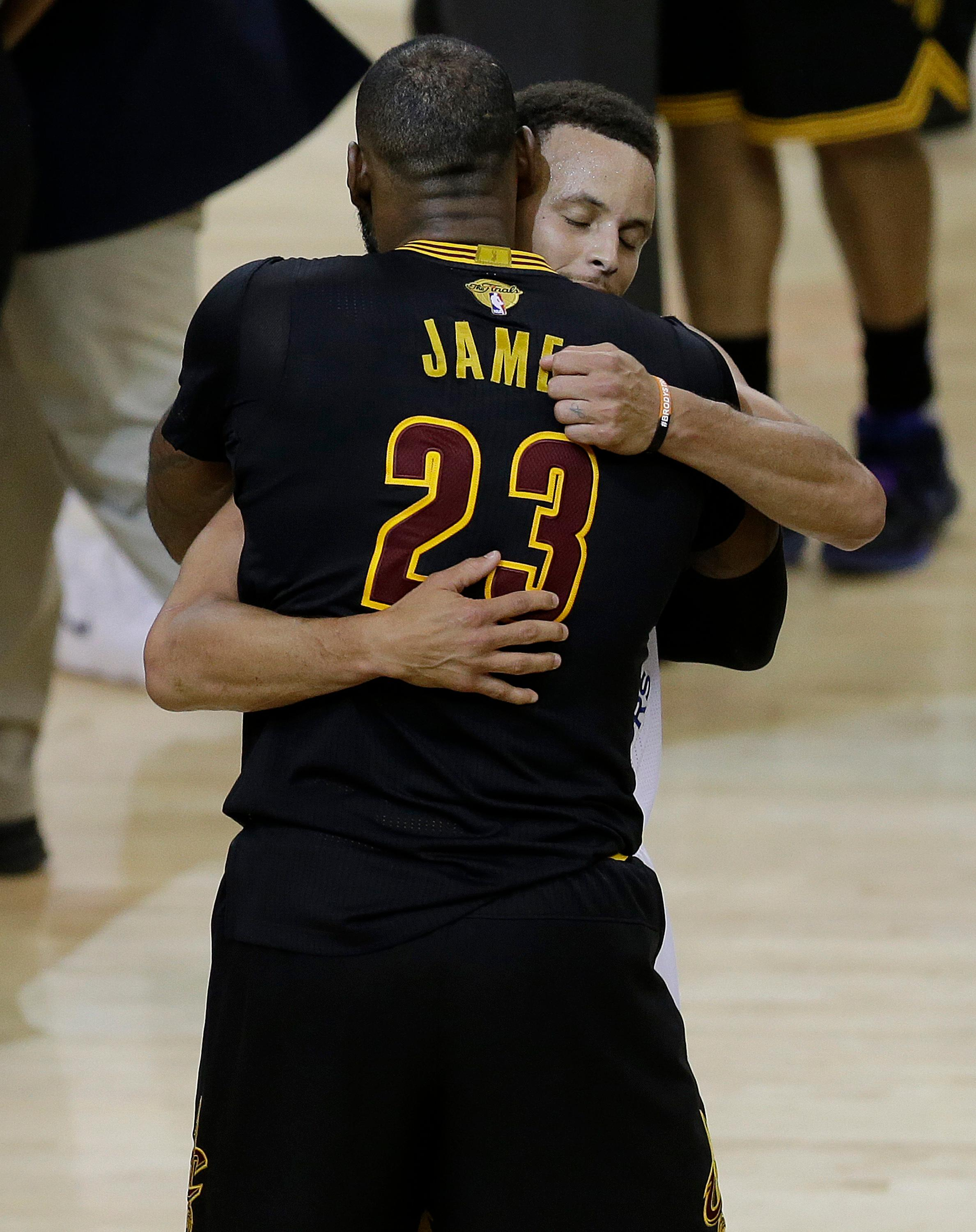 Cleveland Cavaliers forward LeBron James (23) hugs Golden State Warriors guard Stephen Curry after Game 5 of basketball's NBA Finals in Oakland, Calif., Monday, June 12, 2017. The Warriors won 129-120 to win the NBA championship. (AP Photo/Ben Margot)