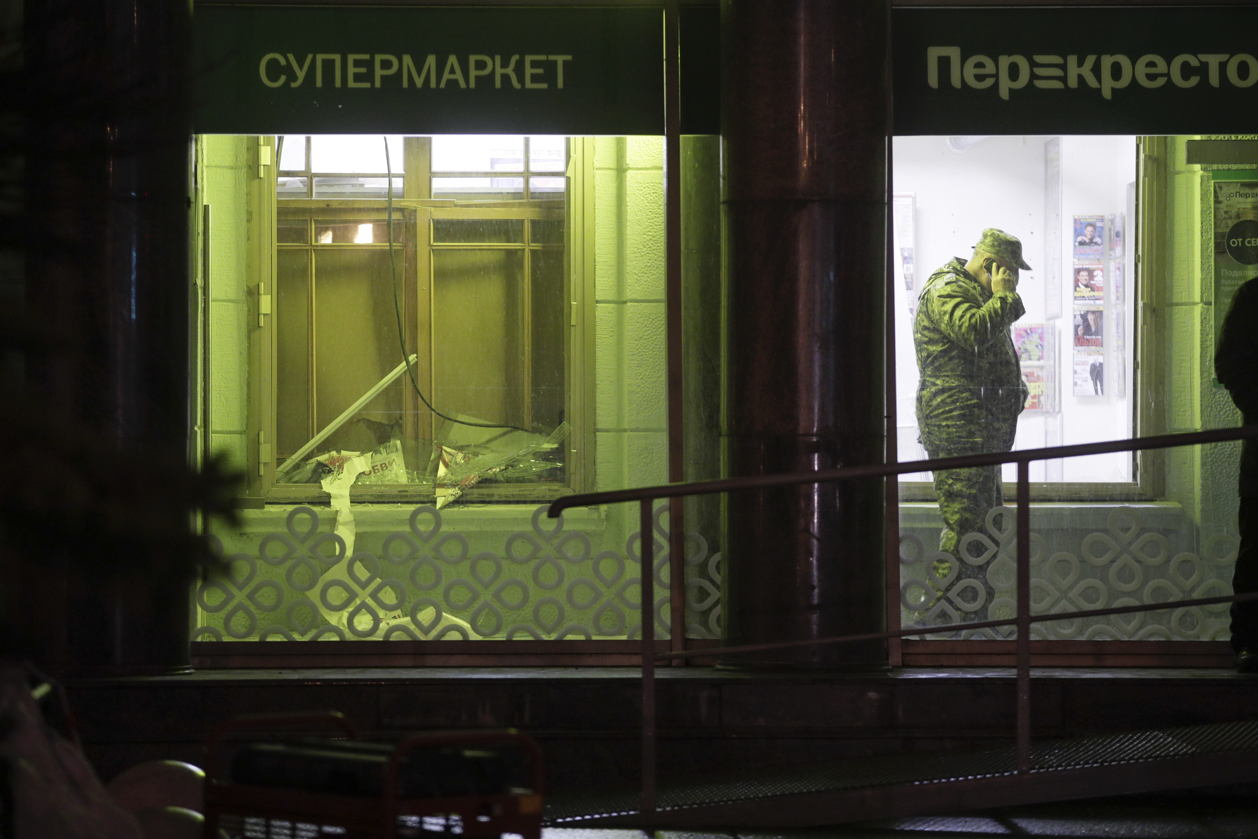 An investigator speaks on the phone inside a supermarket, after an explosion in St.Petersburg, Russia, Wednesday, Dec. 27, 2017. Russian officials say at least 10 people have been injured by an explosion at a supermarket in St. Petersburg. (AP Photo/Dmitri Lovetsky)
