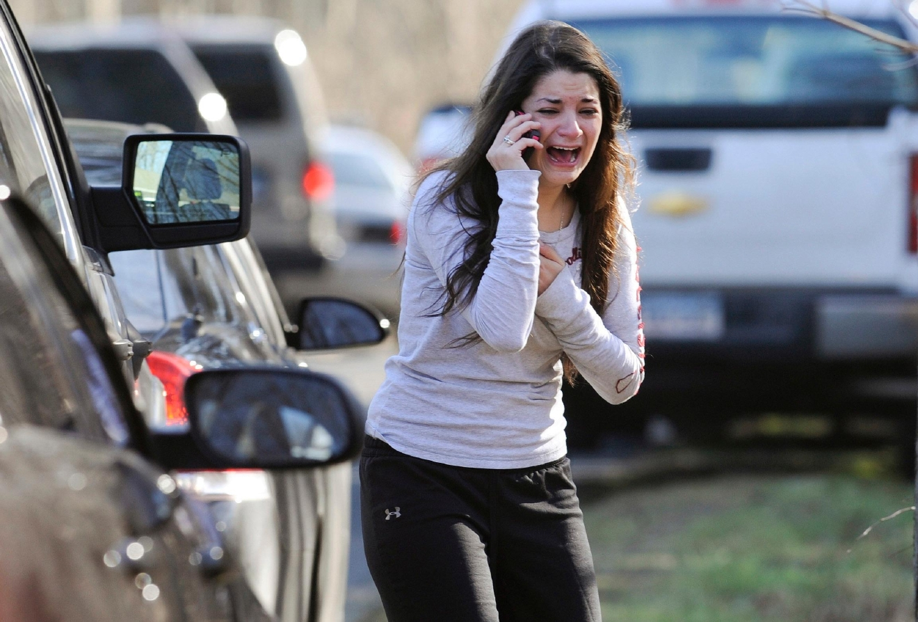 FILE - In this Dec. 14, 2012 file photo, Carlee Soto uses a phone to get information about her sister, Victoria Soto, a teacher at the Sandy Hook Elementary School in Newtown, Conn., after gunman Adam Lanza killed 26 people inside the school, including 20 children. (AP Photo/Jessica Hill, File)<p></p>