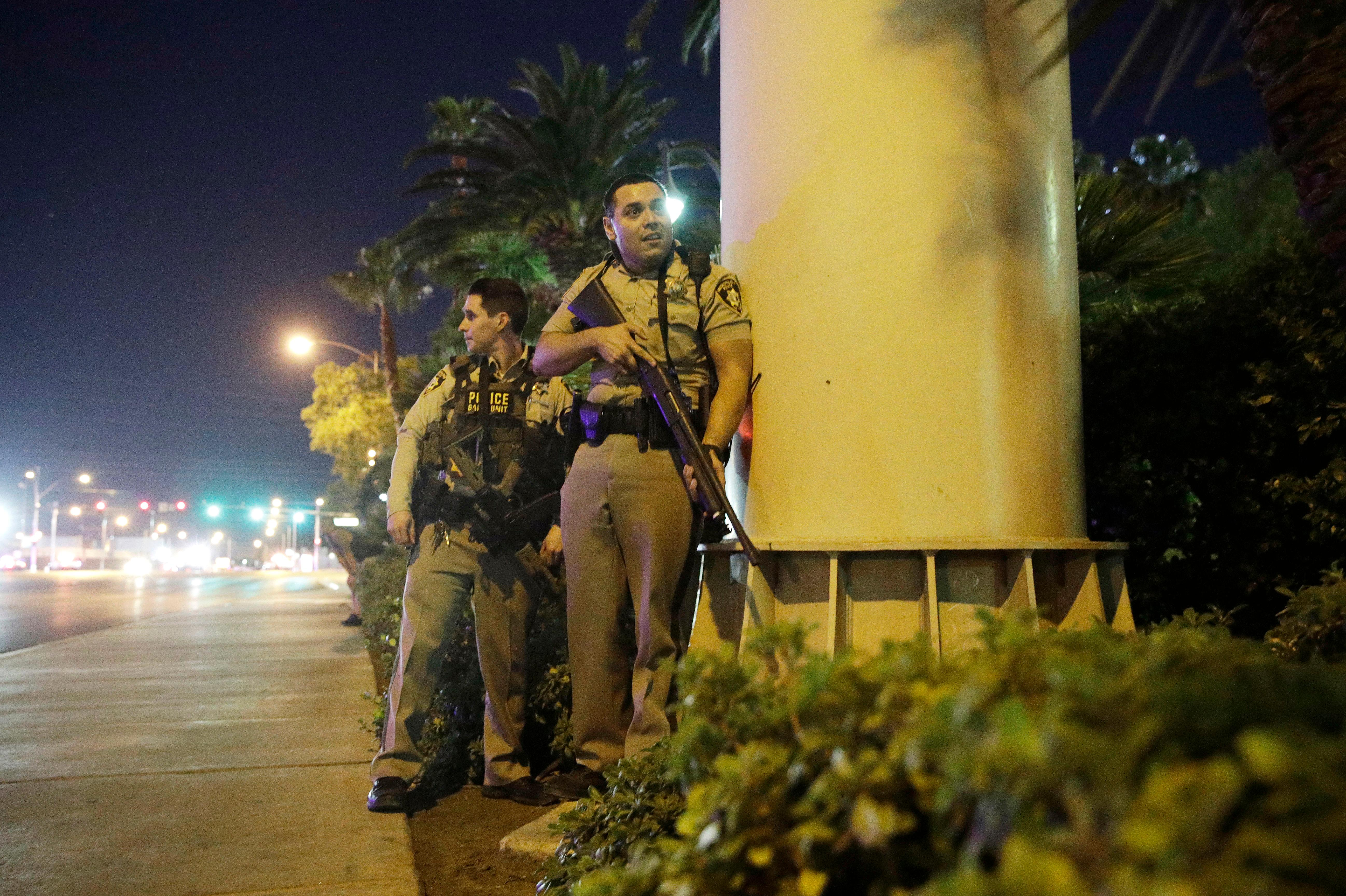 Police officers take cover near the scene of a shooting near the Mandalay Bay resort and casino on the Las Vegas Strip, Sunday, Oct. 1, 2017, in Las Vegas. (AP Photo/John Locher)
