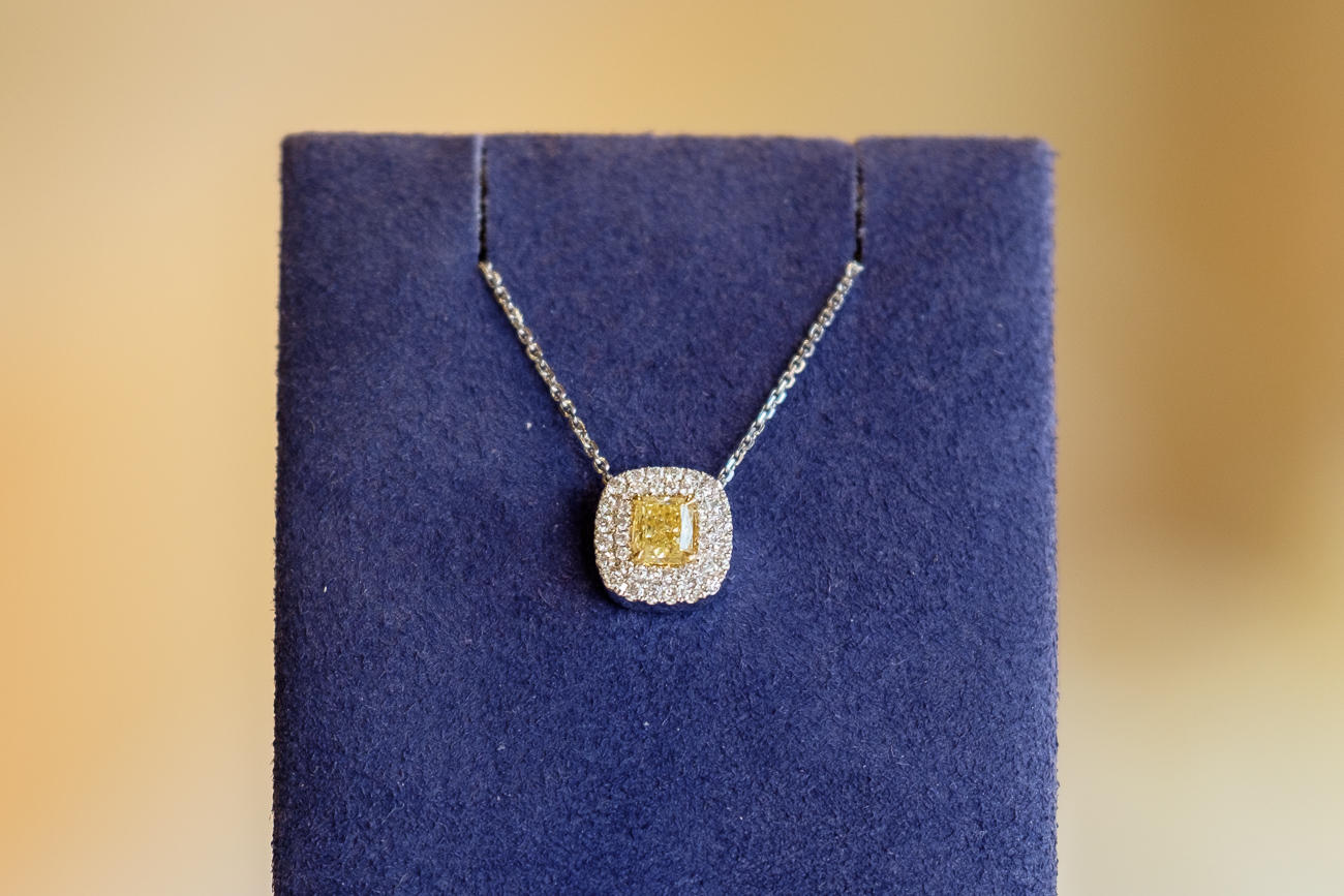 "TWO: This brilliant Halo-style slide pendant is centered by a naturally yellow cushion-cut diamond set in 14k yellow gold. It's surrounded by a double halo of 40 round-cut white diamonds and set on an 18"" fine diamond cut-cable link chain. / $3,950 / Image: Daniel Smyth"