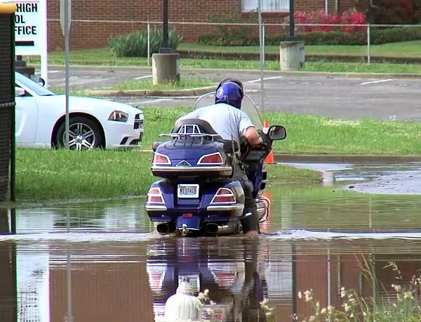 A man attempts to pass through a flooded area near Oxford High School on his motorcycle Wednesday, April 17, 2013.