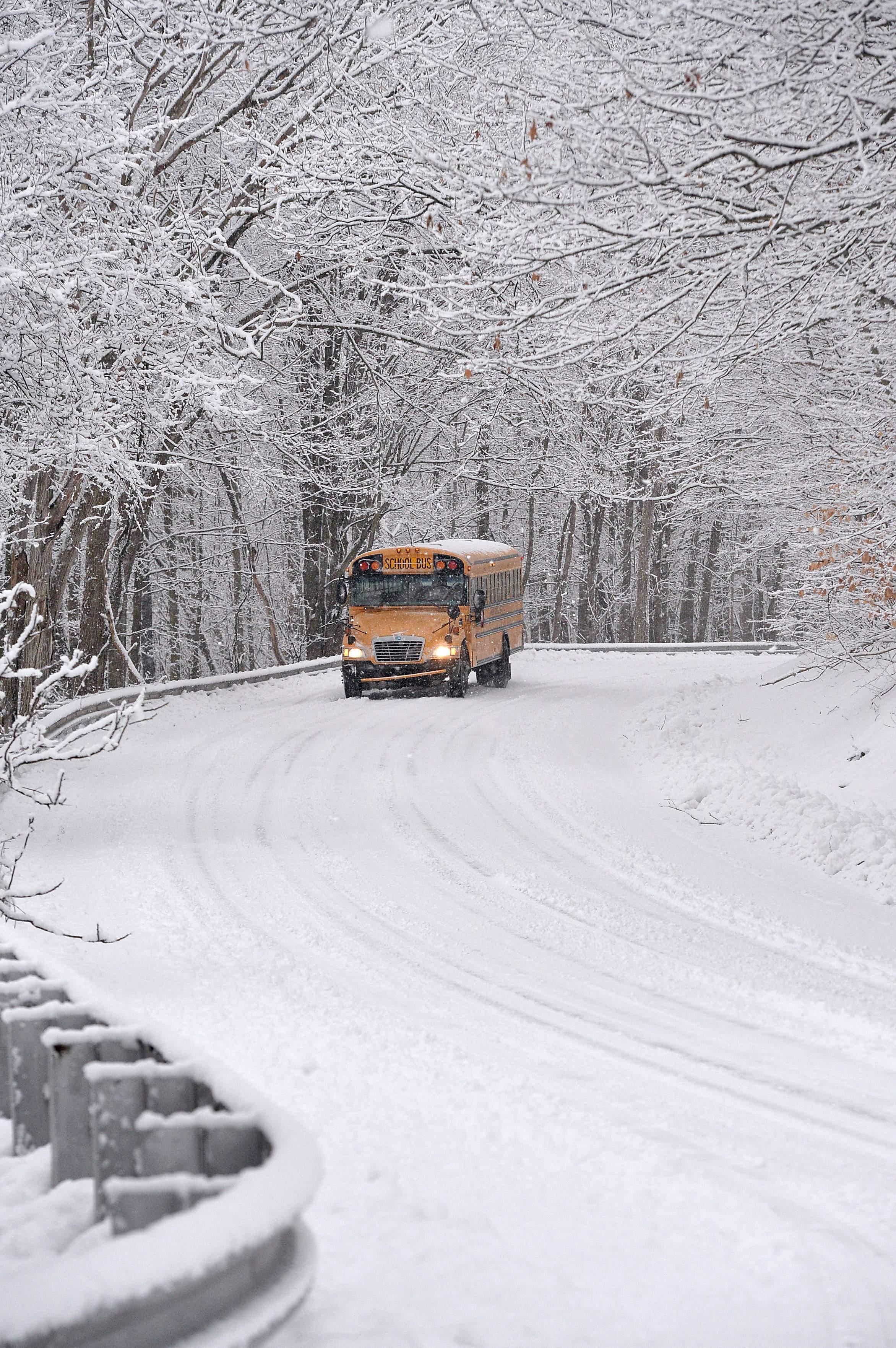 A Fairview School District school bus makes its way west on Van Camp Road in Fairview Township, Erie County, Pa., on March 7, 2018 after several inches of snow fell on the Erie region. (AP Photo/Erie Times-News, Christopher Millette)