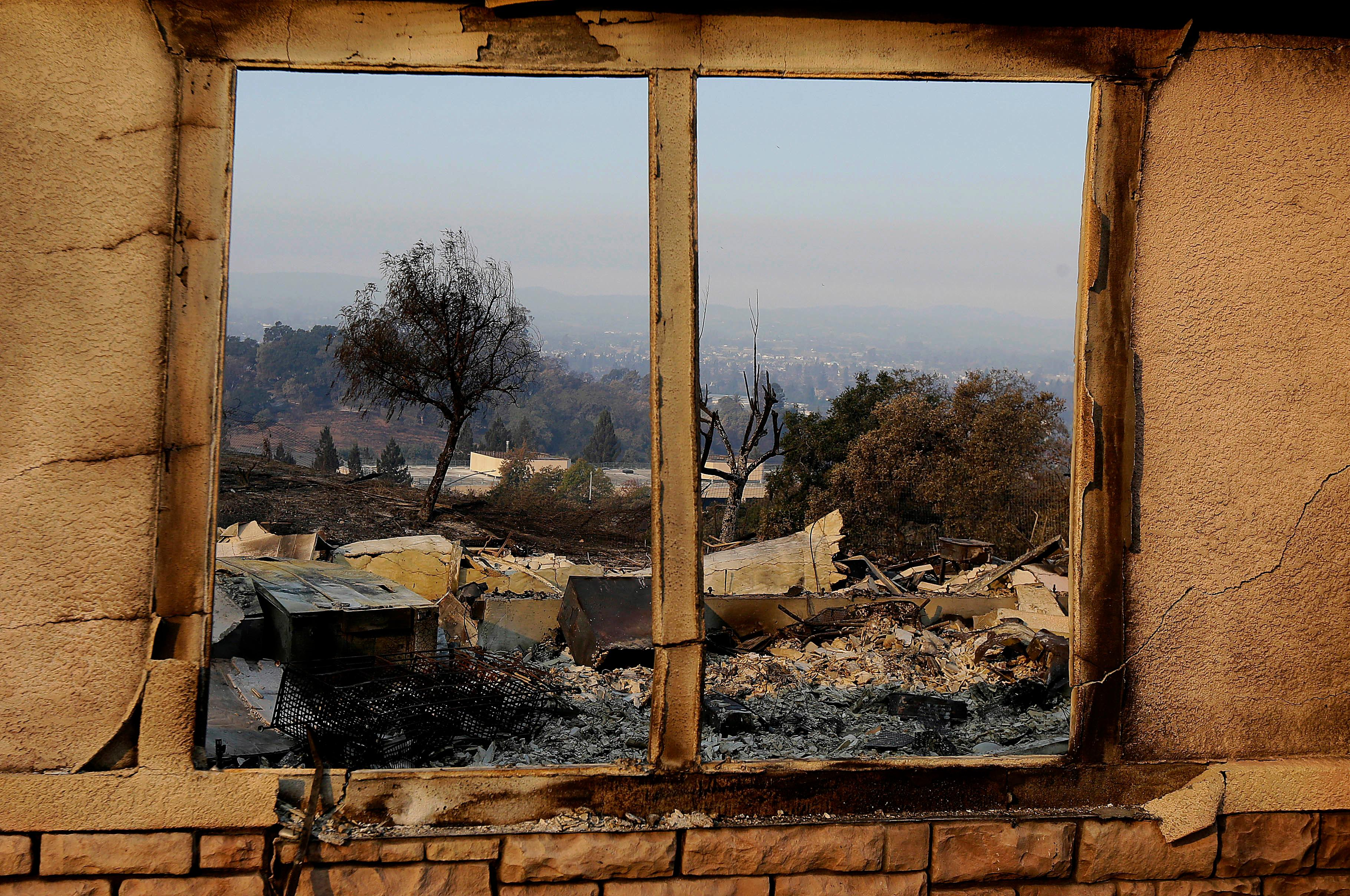 An exterior window frames a home destroyed by fires in Santa Rosa, Calif., Thursday, Oct. 12, 2017. Gusting winds and dry air forecast for Thursday could drive the next wave of devastating wildfires that are already well on their way to becoming the deadliest and most destructive in California history. (AP Photo/Jeff Chiu)