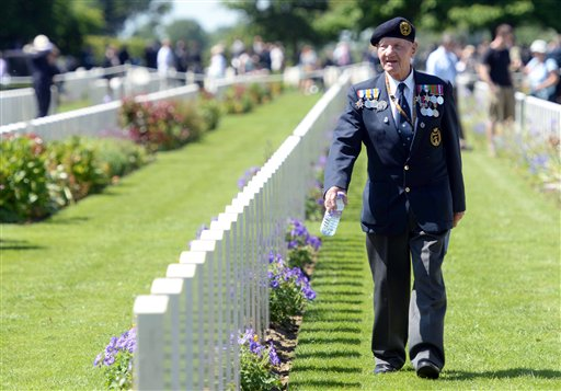 A British veteran walks among headstones before participating in a French-British D-Day commemoration ceremony at the British War Cemetery in Bayeux, France.