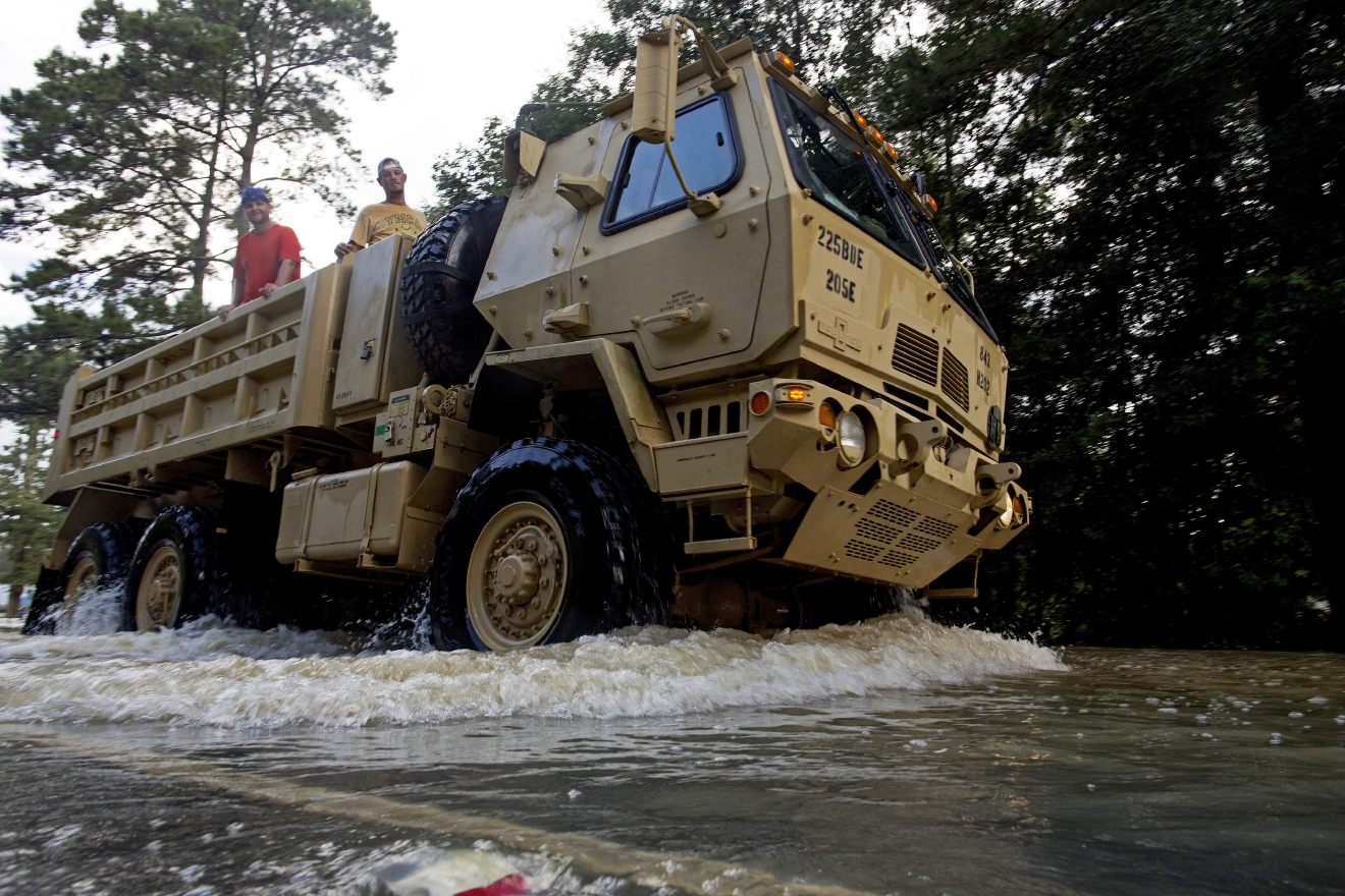 The Louisiana National Guard transports people out of flood hit areas around Walker , La., Monday, Aug. 15, 2016. Although some flood waters have receded roads continue to be difficult to pass with private vehicles. (AP Photo/Max Becherer)