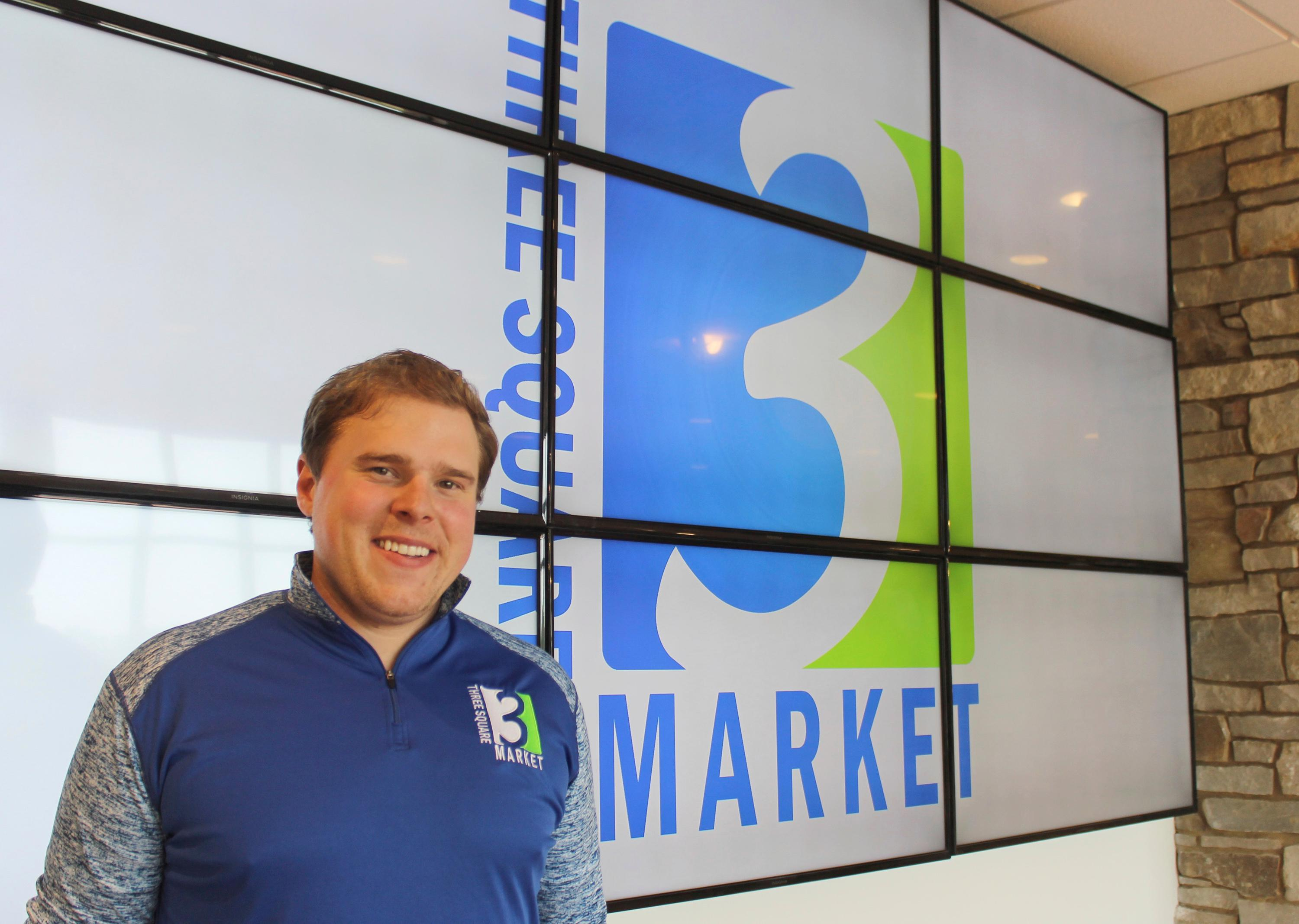 Tony Danna, vice president of international development at Three Square Market, poses in front of the company's logo at its headquarters, Tuesday, July 25, 2017 in River Falls, Wis. The software company is offering to microchip its employees, enabling them to open doors, log onto their computers and purchase break room snacks with a simple wave of the hand. (AP Photo/Jeff Baenen)