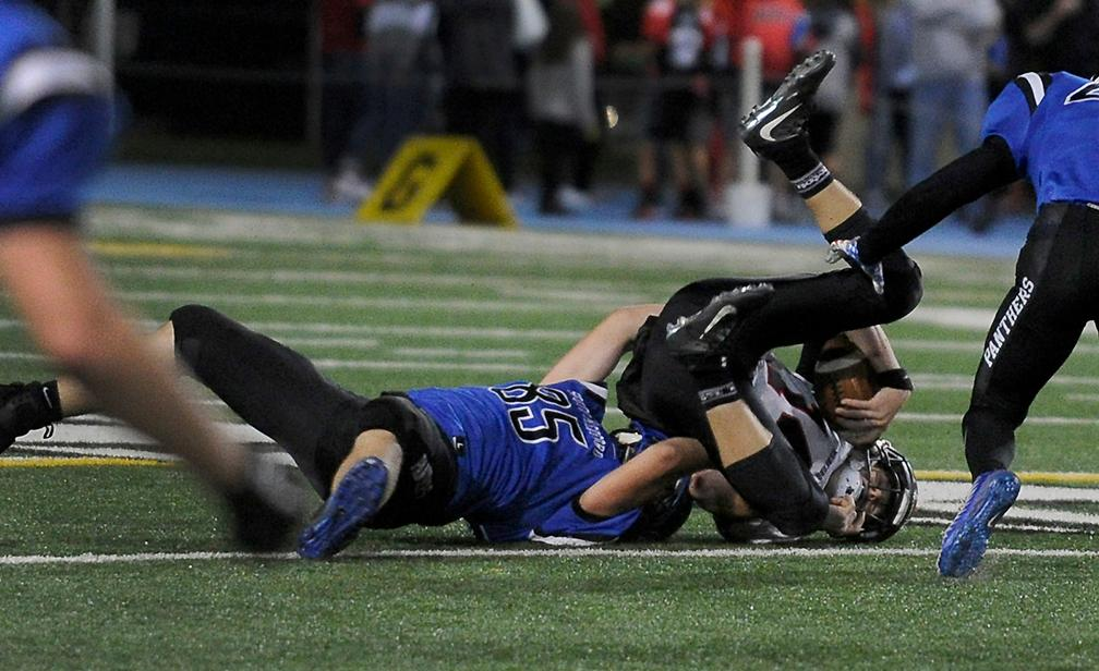 Andy Atkinson / Mail Tribune{ } South's Jaaron Pardy sacks North's Colby Neron for a loss in the 3rd quarter .