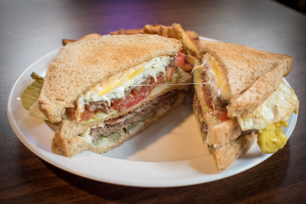 "OTR Legend ""The Jones Burger"":  three pieces of whole wheat toast, two quarter pound burgers with Swiss cheese, bacon, a fried egg, mayo, lettuce, pickle, and tomato. / Image: Phil Armstrong, Cincinnati Refined // Published: 5.15.17"