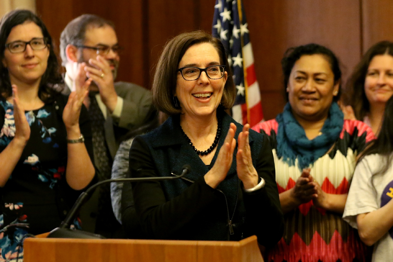 Oregon Gov. Kate Brown celebrates before signing Senate Bill 1532, increasing Oregon's minimum wage according to a tiered system, at the State Capitol in Salem on Wednesday, March 2, 2016. PortlandÂ?s minimum will rise to $14.75 by 2022, suburban areas to $13.50 and rural areas to $12.50. The tiered approach is based on economic factors.  (Anna Reed/Statesman-Journal via AP) MANDATORY CREDIT