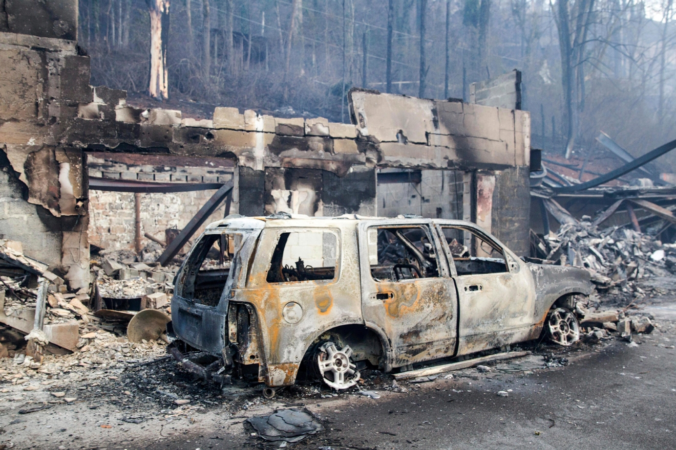 A scorched vehicle sits next to a burned out building in Gatlinburg, Tenn., on Tuesday, Nov. 29, 2016. The fatal fires swept over the tourist town the night before, causing widespread damage. (AP Photo/Erik Schelzig)