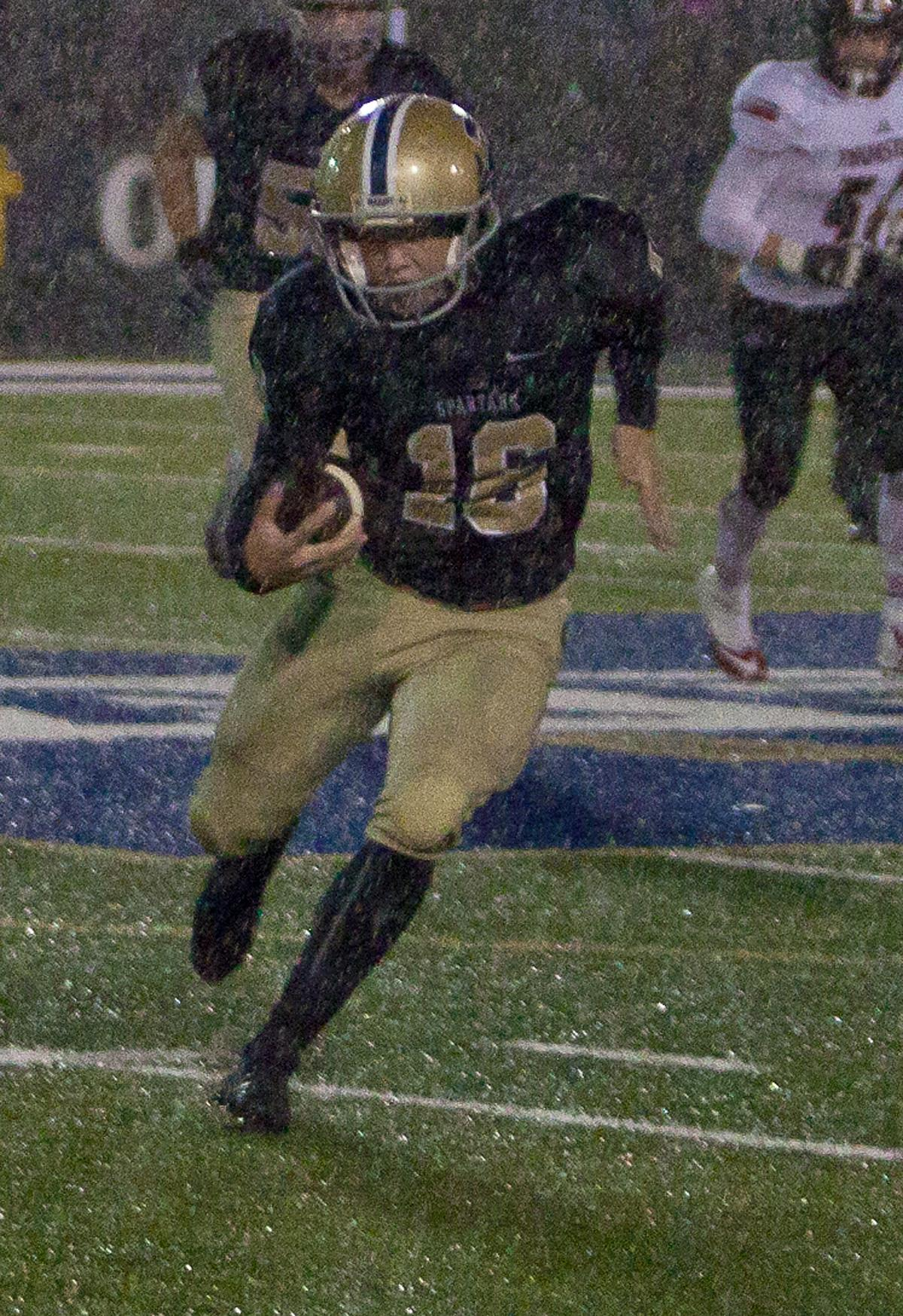 Marist running back Riley Betts (#16) charges through the rain toward the end zone. The Marist Spartans defeated the Thurston Colts 17 to 14. Photo by Ben Lonergan, Oregon News Lab