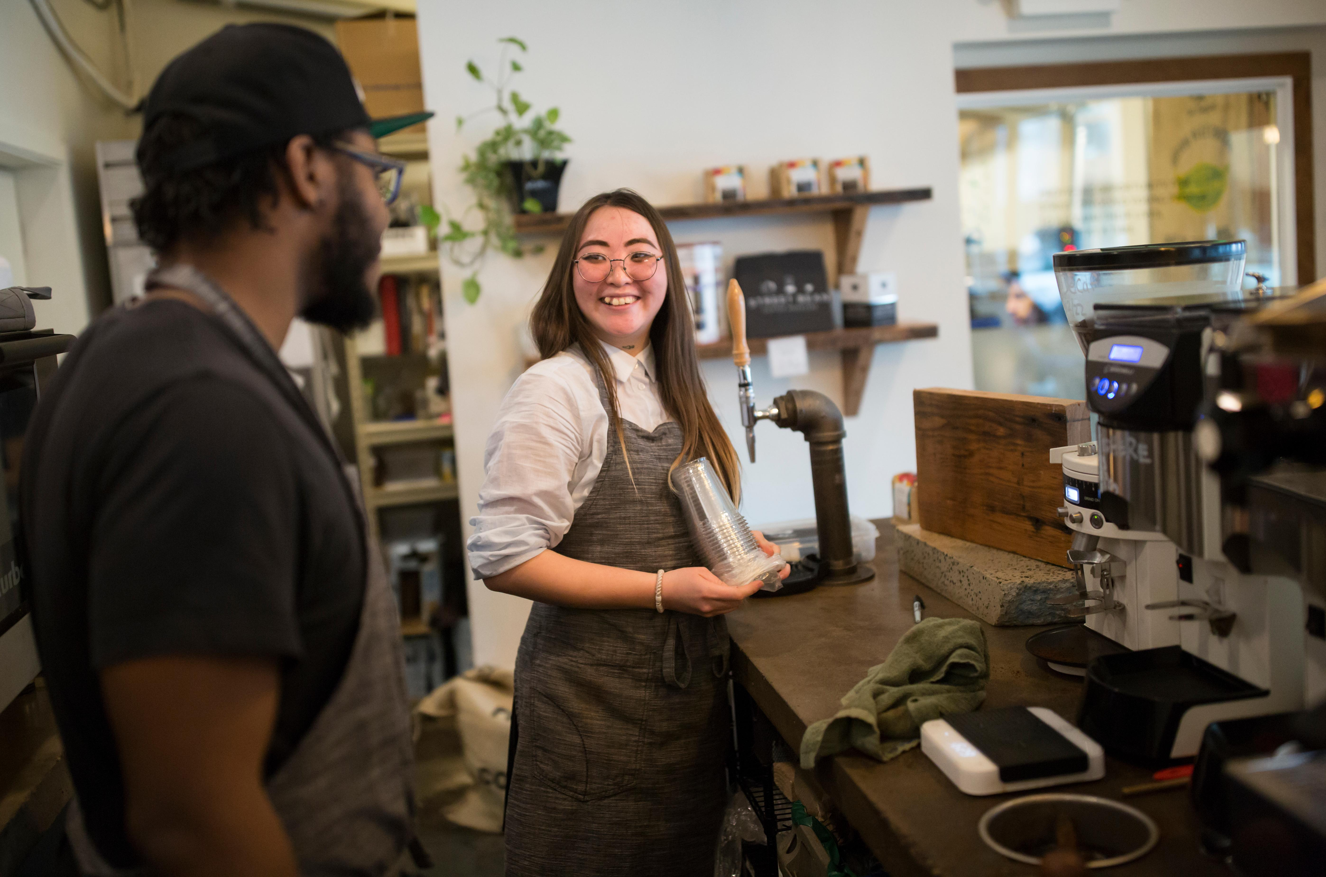 Ynga Chernogradskaia laughs with Shift Supervisor Anthony Harris at Street Bean Coffee Roasters, a local coffee shop and non-profit that's dedicated to providing work opportunities for street-involved youth. (Sy Bean / Seattle Refined)