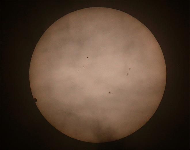 Venus begins to pass in front of the sun, as visible from Hong Kong, Wenesday, June 6, 2012. From the U.S. to South Korea, people around the world turned their attention to the daytime sky on Tuesday and early Wednesday in Asia to make sure they caught the once-in-a-lifetime sight of the transit of Venus. (AP Photo/Vincent Yu)