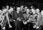 In this March 26, 1949, file photo, University of Kentucky basketball coach Adolph Rupp and his team admire the NCAA basketball title cup after defeating Oklahoma A&M 46-36 in Seattle. Front row, left to right are: Jim Line, Walter Hirsch, Coach Rupp; Ralph Beard, and Clifford Barker. Star center Alex Groza looks over Rupp's shoulder.