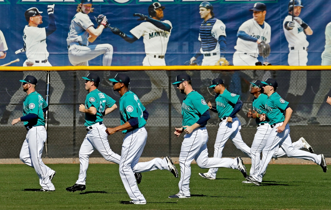 Players for the Seattle Mariners run during spring training baseball practice, Tuesday, Feb. 21, 2017, in Peoria, Ariz. (AP Photo/Charlie Riedel)