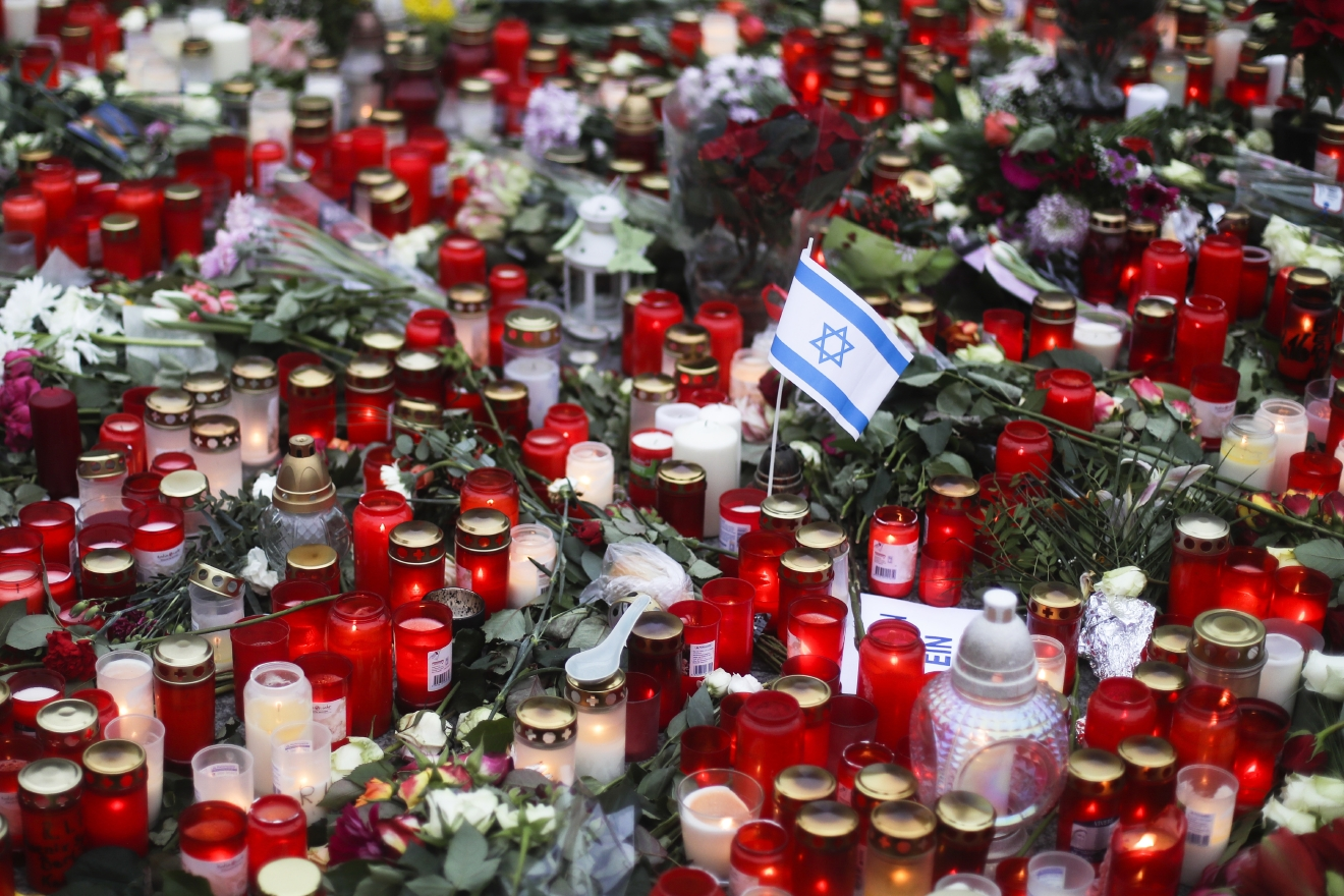 An Israeli flag sitsbetween candles at the Christmas market, three days after a truck ran into the crowd and killed several people, near the Kaiser Wilhelm Memorial Church in Berlin, Thursday, Dec. 22, 2016. (AP Photo/Markus Schreiber)