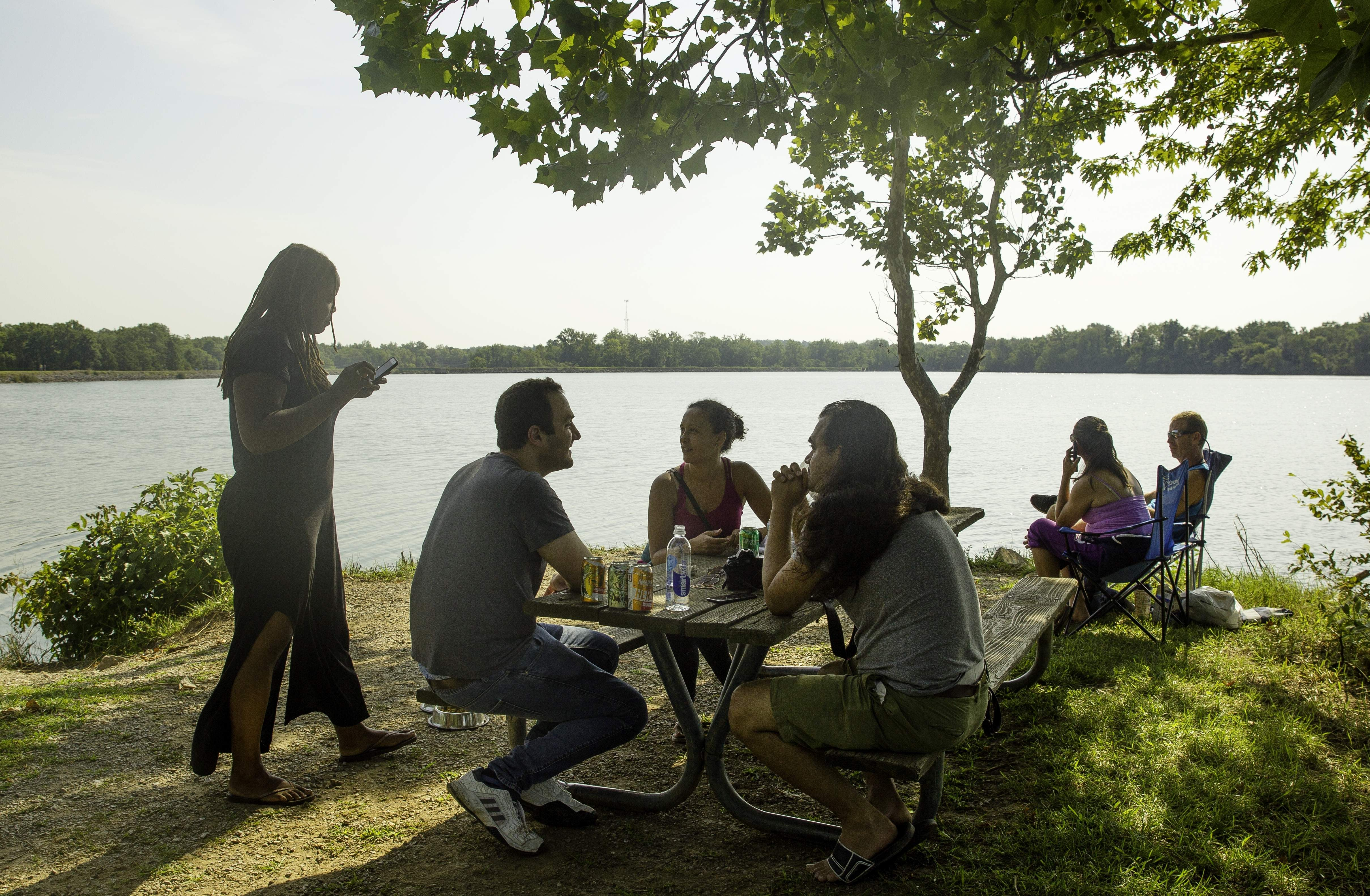 Former college roomates Alex Marson, left, and Cassim Shepard, along with Shepard's wife Heather McGhee, left, and her sister Shannon McGhee visit on a tiny pennisula of land that stretches into the Carbondale Reservoir as they wait for the total solar eclipse Monday, Aug. 21, 2017. Shepard said he's been waiting to view the eclipse since he saw a commercial for the Mitsubishi Eclipse as a nine-year-old that advertised the 2017 event. 'I thought the future would be here,' Shepard said, who also thought we'd be traveling in solar-powered vehicles to the moon. [Ted Schurter/The State Journal-Register]