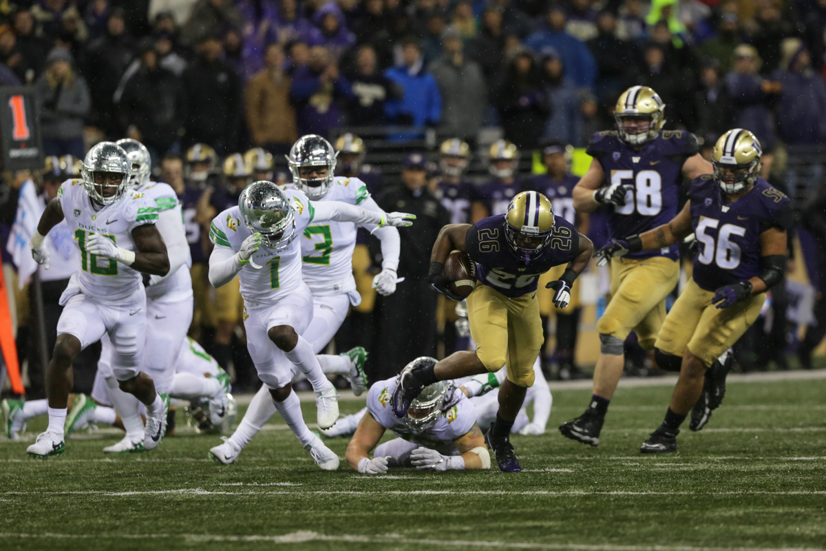 Washington running back Salvon Ahmed (#26) runs past the Oregon defense heading for a touchdown.  The Oregon Ducks fell to the Washington Huskies 38 - 3 on a cold and rainy night in Seattle, Washington.  Oregon opened the game with a field goal on their first drive and was held scoreless from then on.  Photo by Austin Hicks, Oregon News Lab