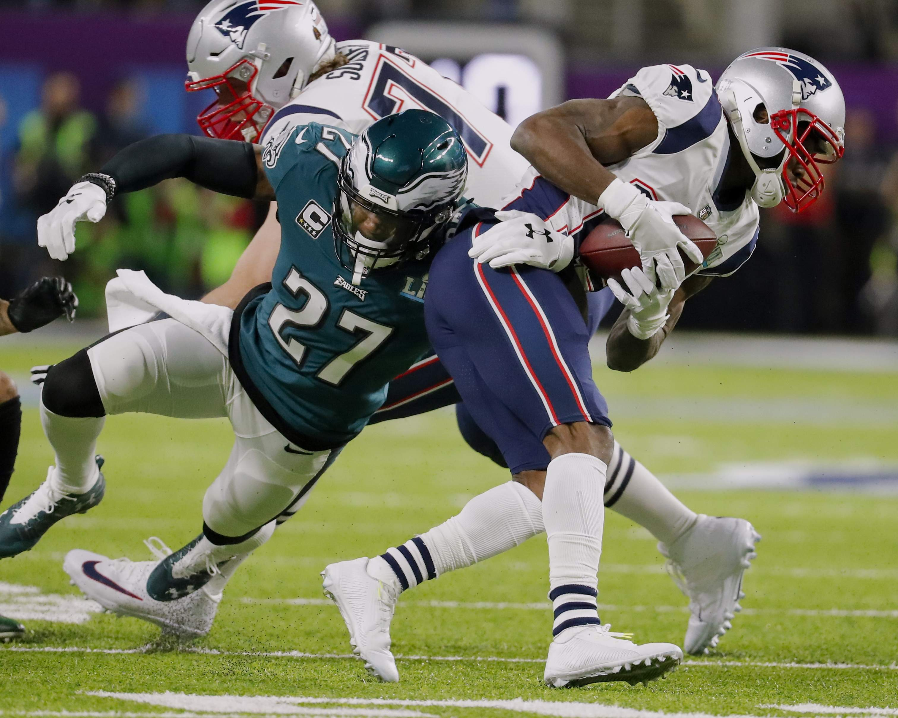 Philadelphia Eagles strong safety Malcolm Jenkins (27), tackles New England Patriots wide receiver Brandin Cooks (14), during the first half of the NFL Super Bowl 52 football game, Sunday, Feb. 4, 2018, in Minneapolis. (AP Photo/Charlie Neibergall)