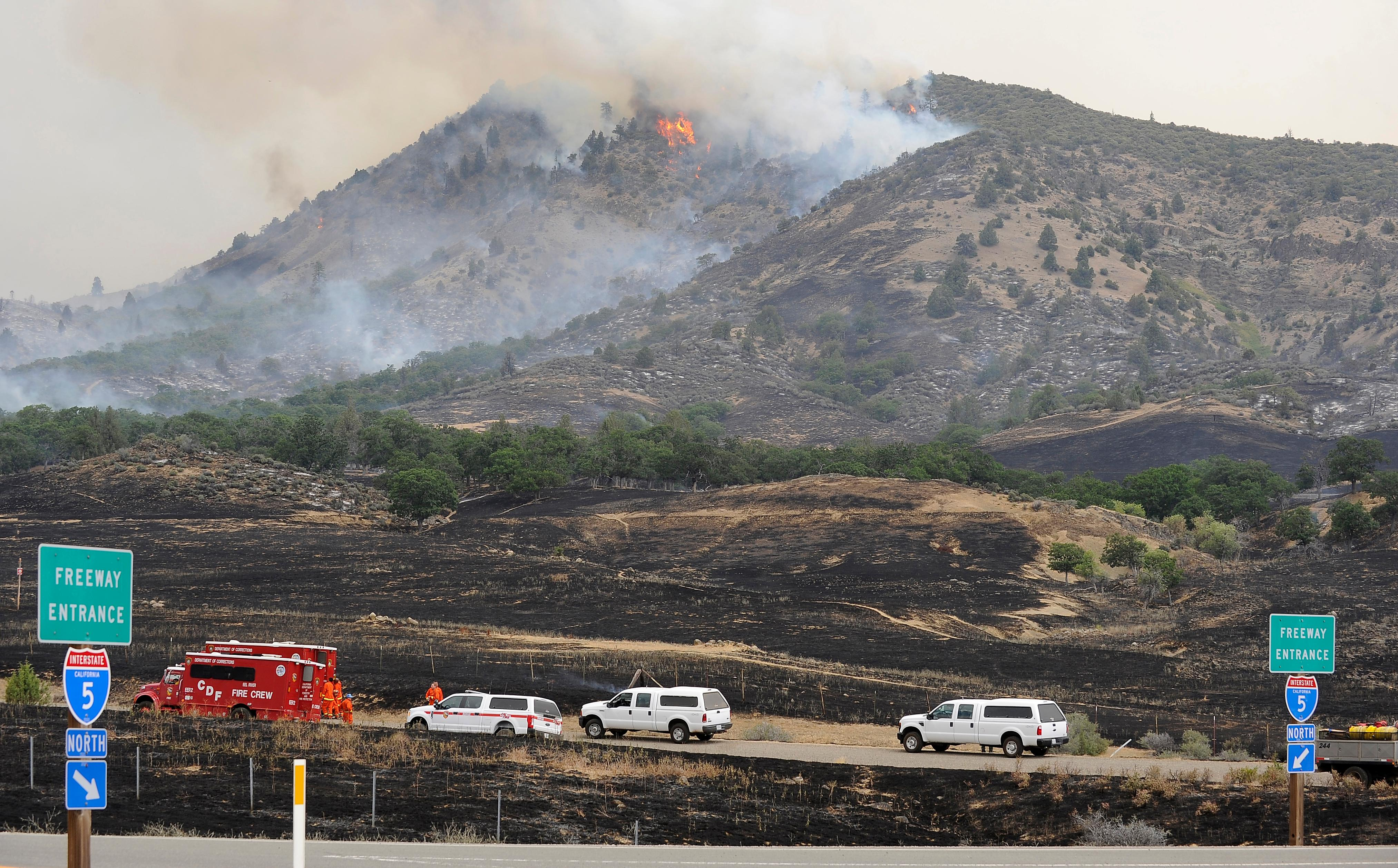 Andy Atkinson / Mail TribuneNorthern California fire crews watch a blaze move up a hill off Baily Hill Road near the I-5 interchange just miles south of the Oregon-California border Friday afternoon.