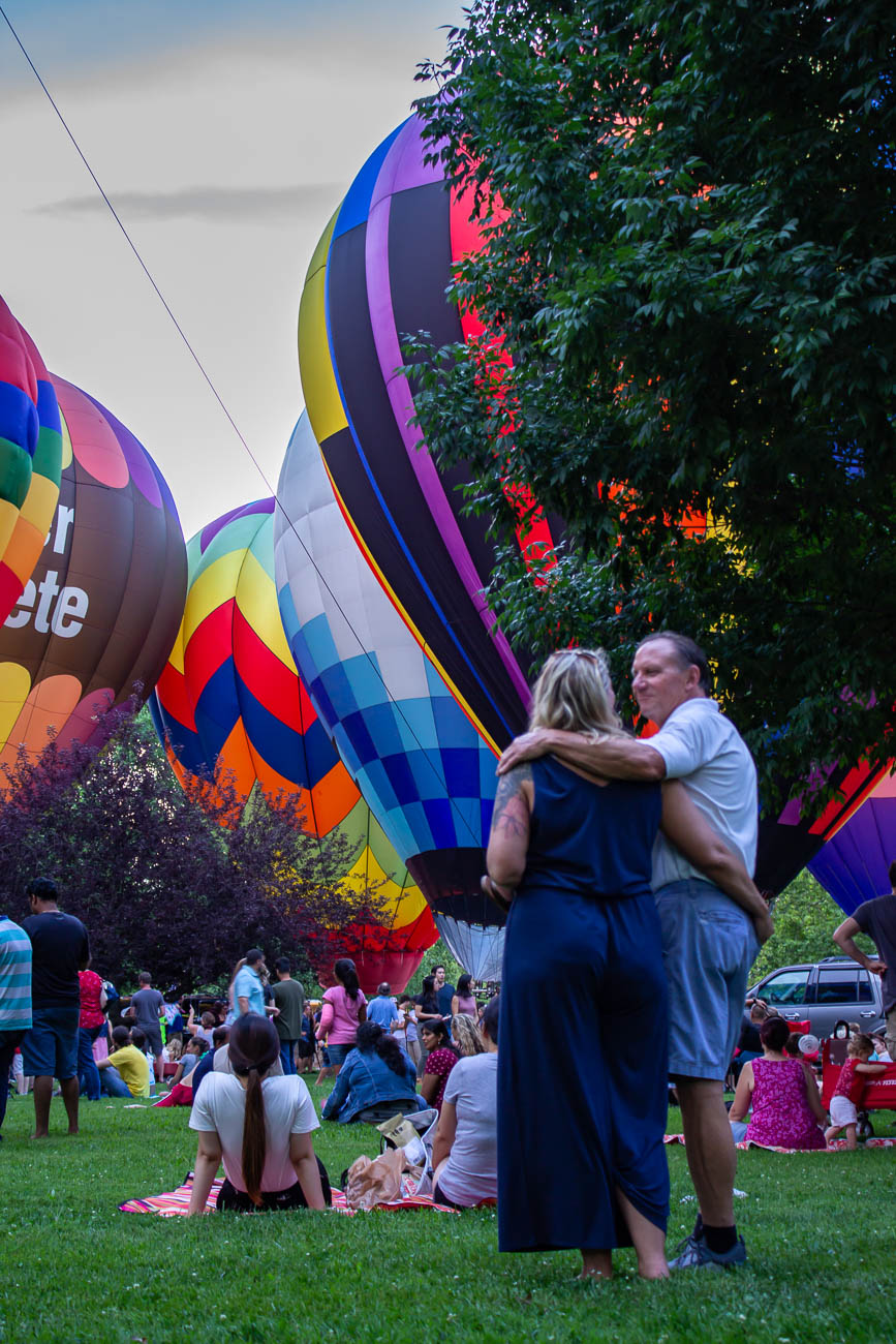 A couple amidst massive, colorful hot air balloons at the Balloon Glow at Coney Island / Image: Katie Robinson