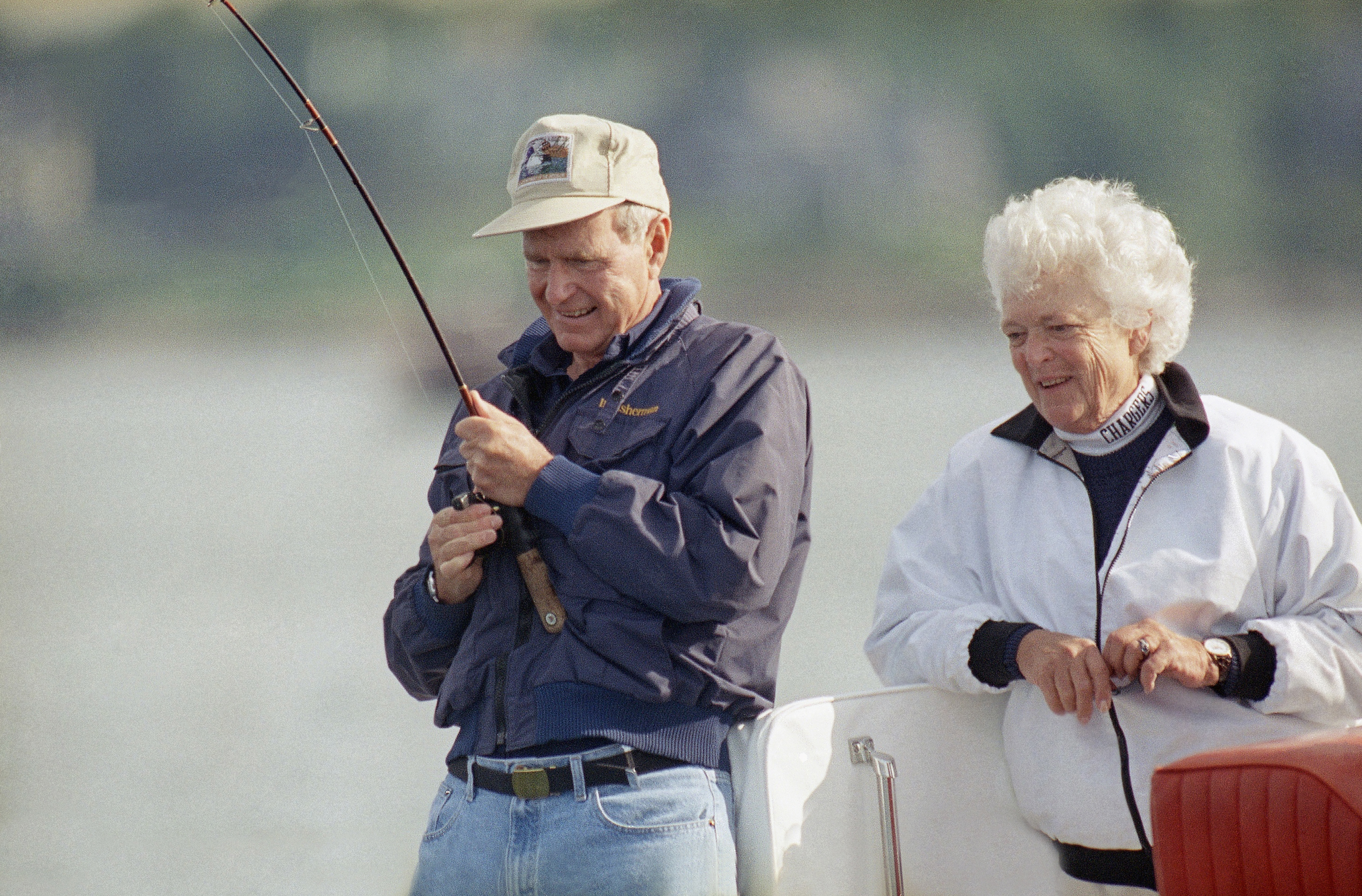 "FILE - In this Aug. 7, 1991, file photo, Barbara Bush watches as President George Bush reels in a fish aboard their boat Fidelity, just off shore from their Vacation home at Walkers Point in Kennebunkport, Me. Former first couple George and Barbara Bush's relationship is a true love story, described by granddaughter Jenna Bush Hager as ""remarkable."" They met at a Christmas dance. She was 17. He was 18. Two years later they were married. Now 73 years later, with Barbara Bush declining further medical care for health problems, they are the longest-married couple in presidential history. (AP Photo/Susan Walsh, File)"