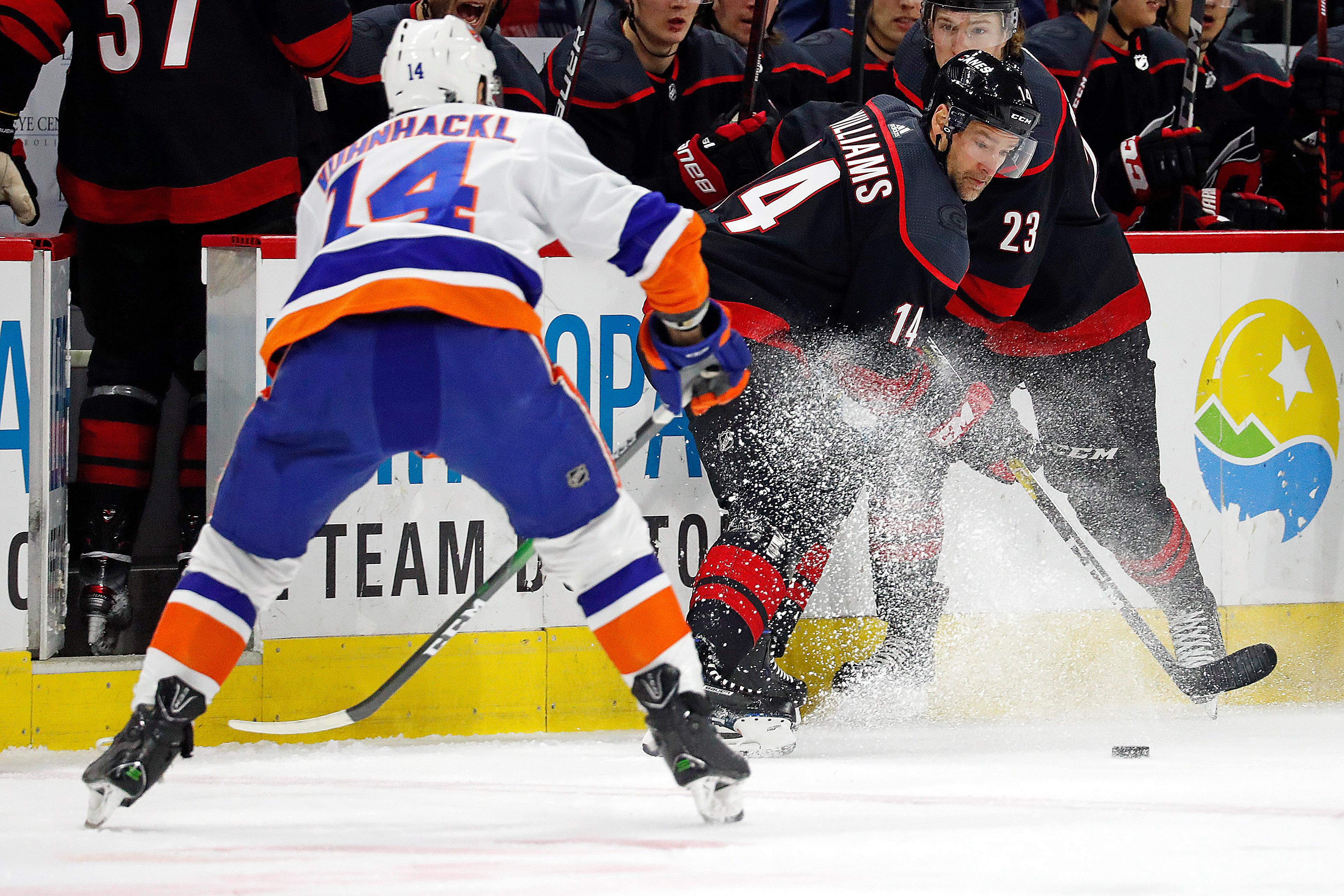 Carolina Hurricanes' Justin Williams, center, plays the puck in front of New York Islanders' Tom Kuhnhackl, left, of Germany, during the first period of an NHL hockey game in Raleigh, N.C., Sunday, Jan. 19, 2020. (AP Photo/Karl B DeBlaker)