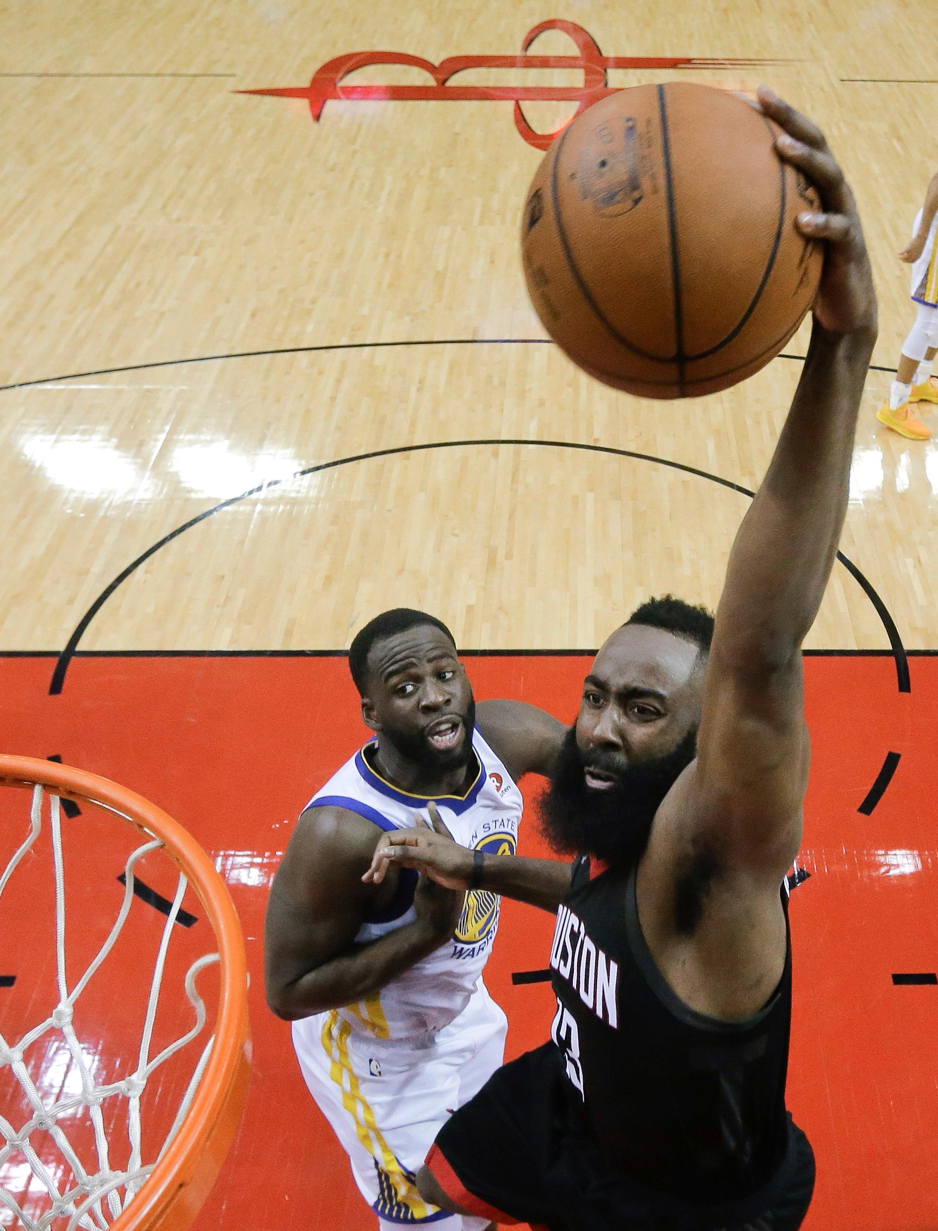 Houston Rockets guard James Harden scores over Golden State Warriors forward Kevon Looney in the first half during Game 5 of the NBA basketball playoffs Western Conference Finals, Thursday, May 24, 2018, in Houston. (AP Photo/David J. Phillip)