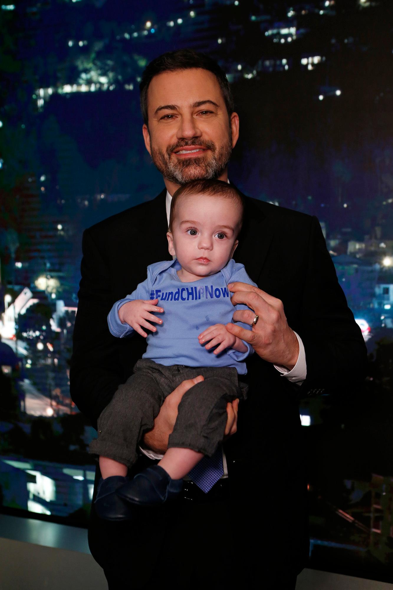 "This Dec. 11, 2017 image released by ABC shows host Jimmy Kimmel with his son Billy on the set of ""Jimmy Kimmel Live!"" Kimmel held his baby son as he returned to his late-night show after a week off for the boy's heart surgery. Kimmel kept up his ardent advocacy Monday night, urging Congress to restore the Children's Health Insurance Program, which has been left unfunded and stuck in a political stalemate since September. (Randy Holmes/ABC via AP)"